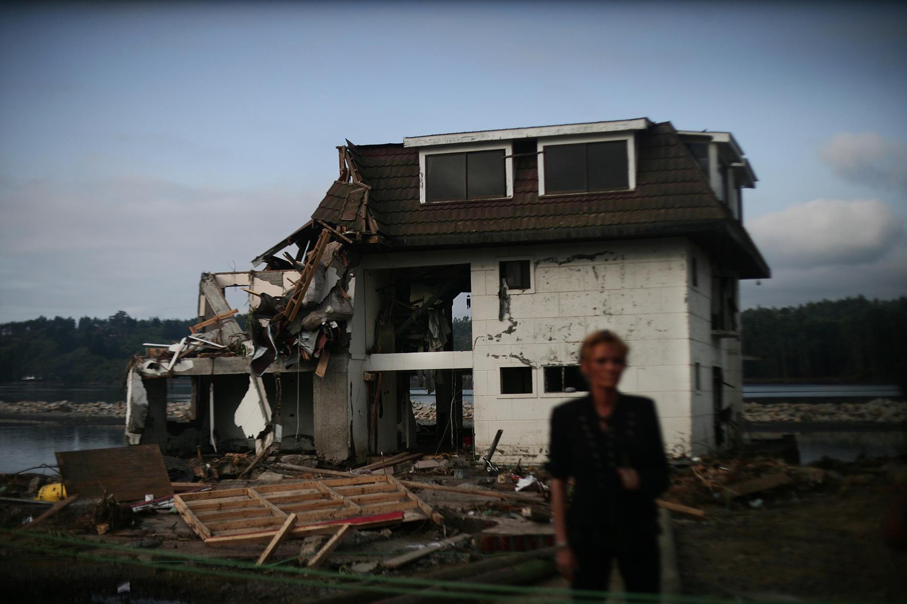 una periodista raliza un enlace enfrente de un hotel destruido por el tsunami en constitucion