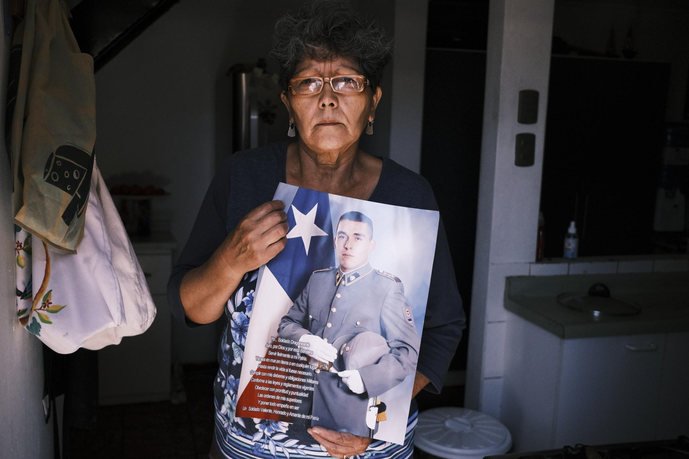 "Santiago, Chile, 2020. Alicia González, holds her favorite picture of her son Danilo wearing his military uniform. She explains in an interview: ""Danilo was not a delinquent. He was going to work and made a mistake. He should be alive but instead was murdered by the government's hitmen who pretend that wearing a uniform gives them some power. I want justice."" During the night of March 4, 2020, Danilo crashed his car into a police patrol car at a tollbooth station. An ensuing argument ended with Danilo being shot and killed by the police. Later videos from witnesses show how after the crash, cops put handcuffs on Danilo, and while he was on the ground begging for his life, one fired his gun at him."