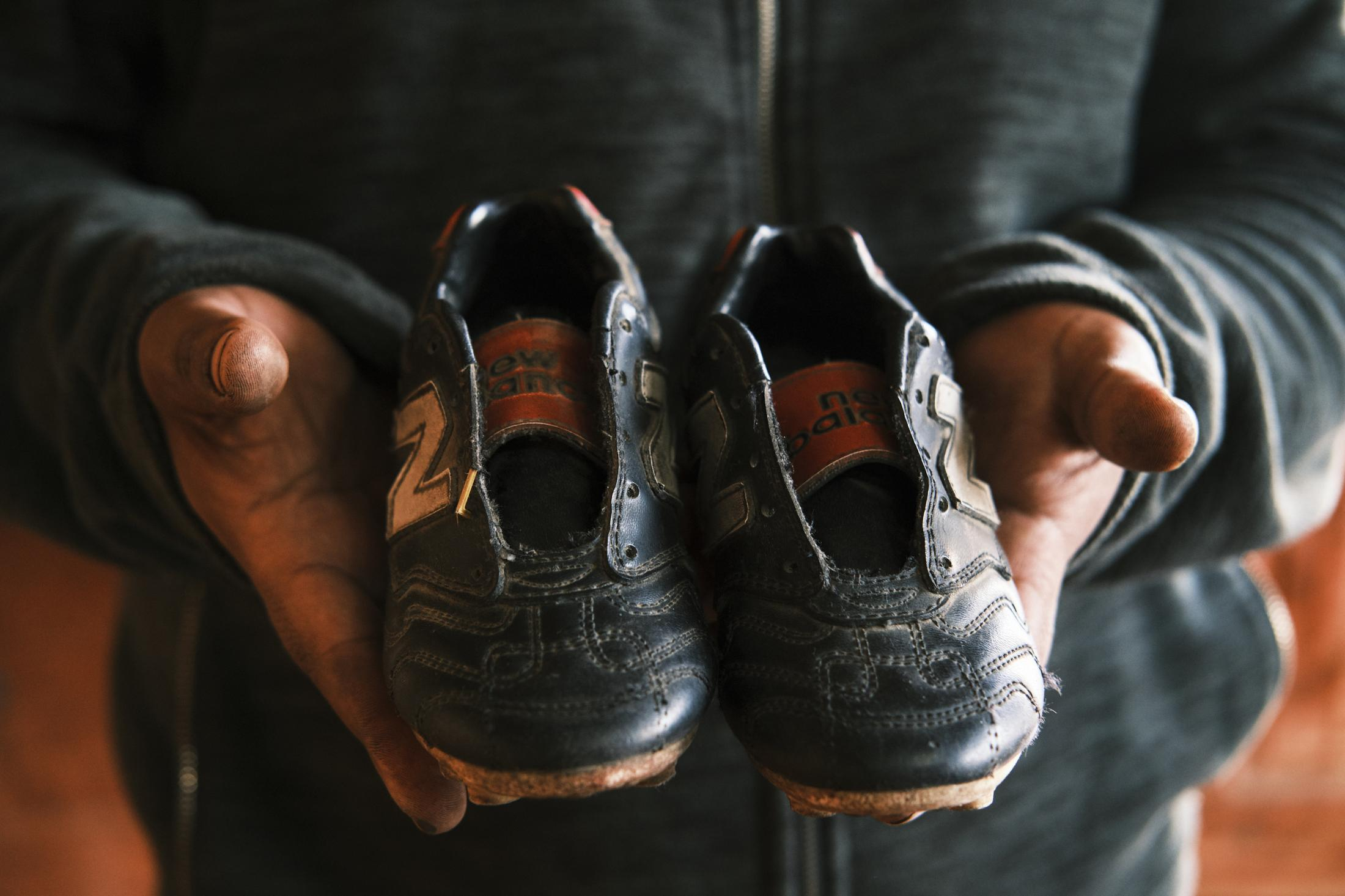 "Coquimbo, Chile, 2020. Victor Briceño, the stepbrother of a teenager killed during a riot, holds a pair of old soccer shoes that were used by his brother when he was a kid. He explains in an interview, ""I bought these shoes for him when he was five, I always kept them at home. Kevin came to live with us when he was a baby and was a brother to me. I raised him. When the army murdered him, I put the shoes in the coffin, but I decided to keep them with us forever at the last minute."" Kevin Gómez, a 24-year-old student, was shot and killed by a member of the military forces deployed during a state of emergency on the first week of riots and lootings in the region of Coquimbo, in the north of Chile. Kevin was shot in the back with his hands in the air when the military assumed he was looting a strip mall with other protesters. The investigation is still ongoing after a year."