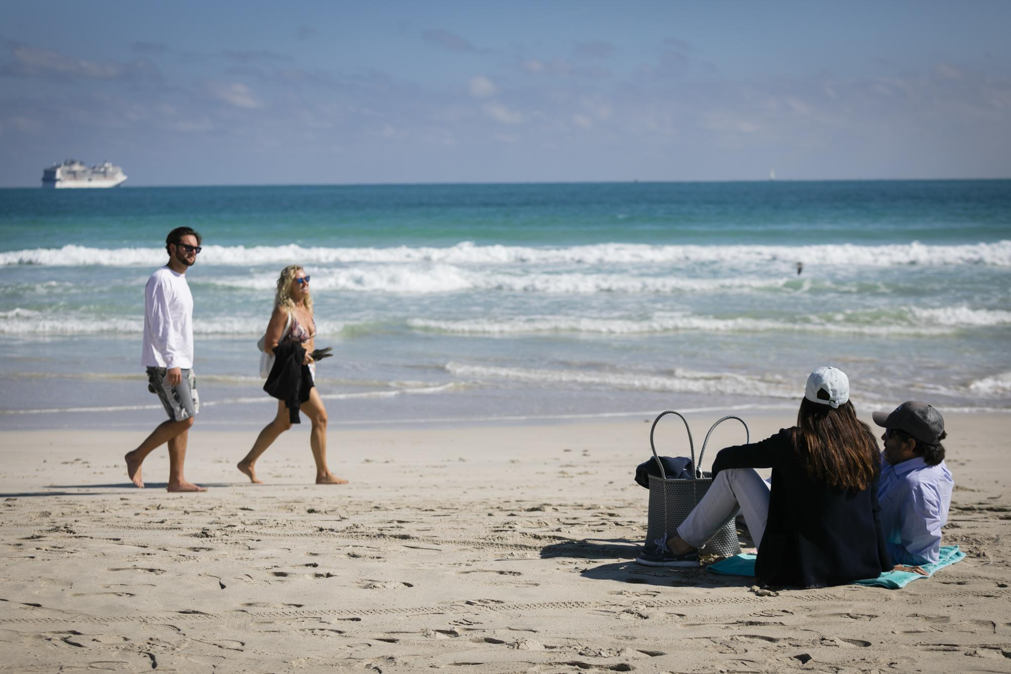 People are seen on the beach, in Miami Beach, Florida on January 10, 2021. Eva Marie UZCATEGUI