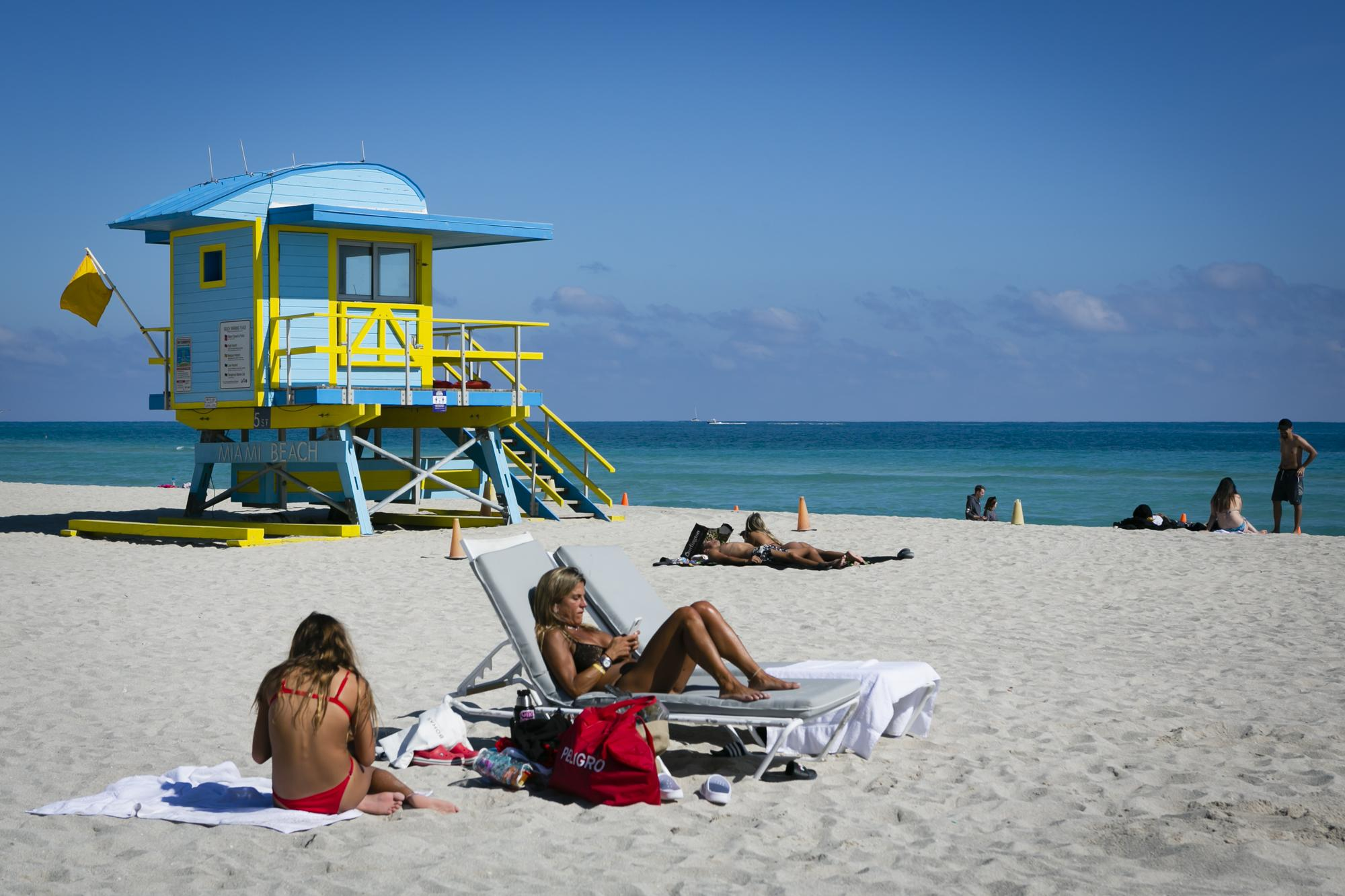 People sunbath at the beach, in Miami Beach, Florida on January 10, 2021. Eva Marie UZCATEGUI