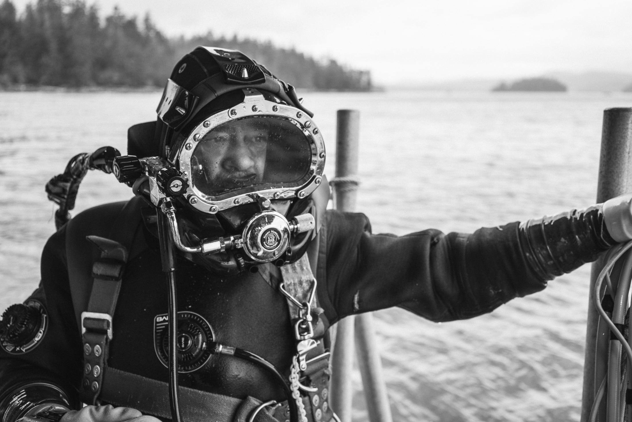 """Meet Curtis Brown. Don't let his soft smile and kind disposition fool you. He is a seasoned geoduck hustler on the Klawock dive scene. His military roots are apparent in the attention and care he brings to his craft. He is patient, careful, and deliberate, which is important when you are weighed down 50 feet in frigid waters. """"Geoducks like the sugar sand,"""" he says. """"The barnacly-broken up- shell sand that when you toss it up, it'll all settle down. That's where you'll find them."""" Curtis slaps on his fishing costume — a dry suit and layers of fleece — with precision. He spits into his mask, rubbing the glass clear before falling gracefully into the drink."""