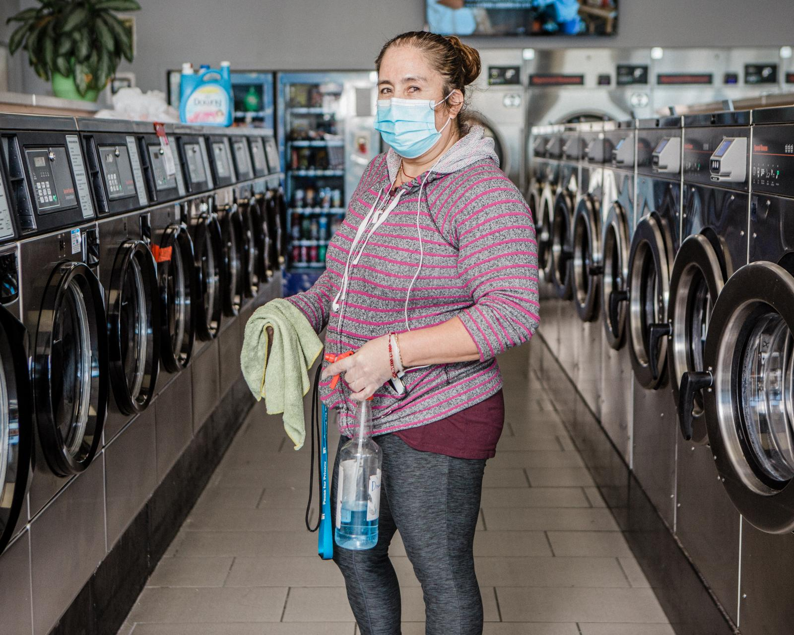 Yolanda Compass Palacio stands for a portrait in the laundry mat where she works three days a week, She has another job at night as a custodian at an office building. Thursday, December 17, 2020