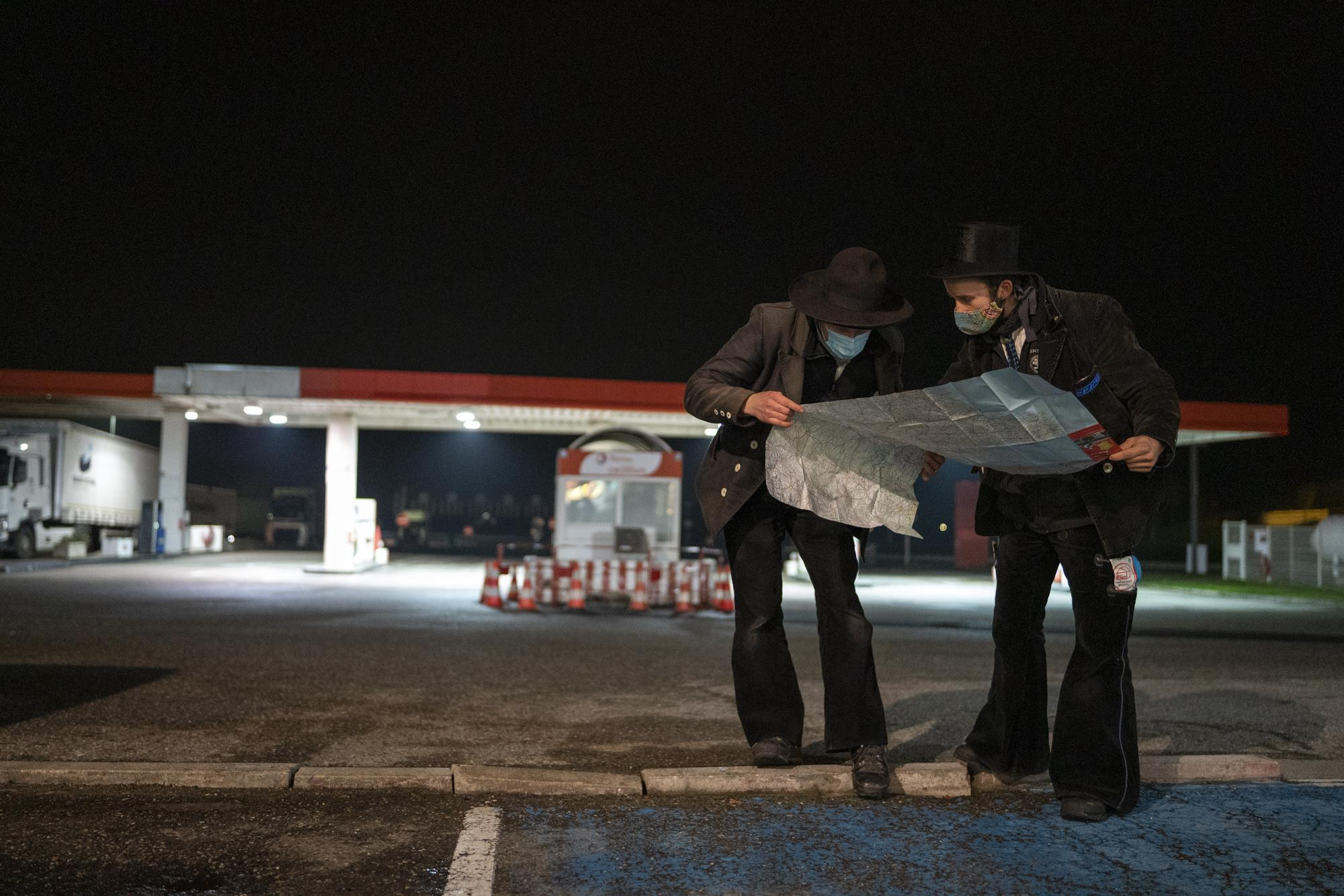 Ben (L) and Matthias check the map of France at the empty service Aire de la Porte d'Alsace on the A36 after Mulhouse, France, in the late afternoon of December 2, 2020. They reunited there after getting on different lifts near Strasbourg.