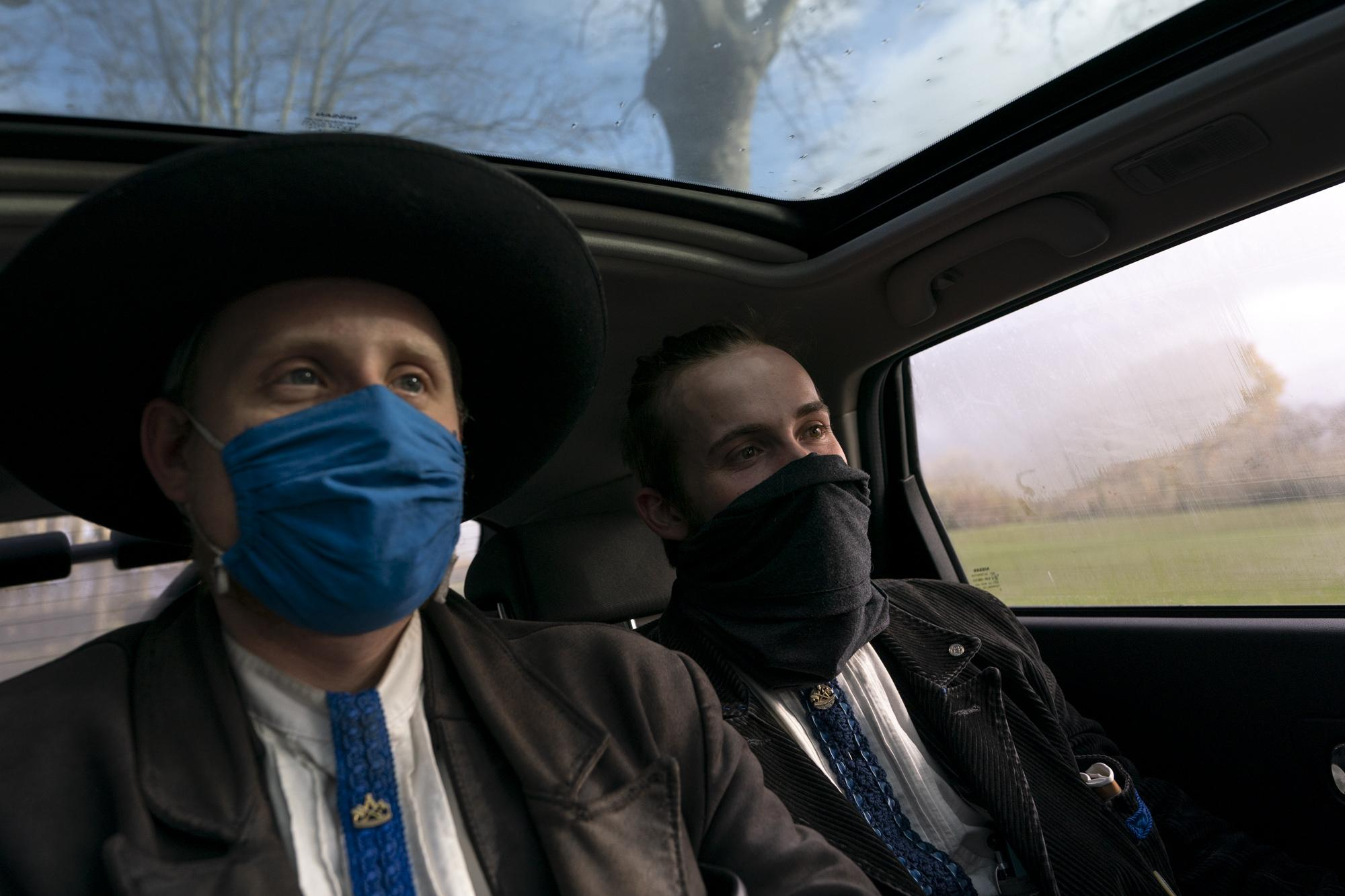 Ben (L) and Matthias sit in the backseat of Stéphane's car, as outside the rain starts again, near Gaillac, France, on December 12, 2020. Stéphane, a cook for star restaurants, saw the two young men walking along the road on his way to Gaillac, and later told them that as he saw them again while driving back home, he had to stop to learn about their costumes. Discovering about this tradition made him visibly happy and touched him profoundly during the short time they shared in the car trip from Gaillac, via Lisle-sur-Tarne until Rabastens, where he drove them extra 16 km.