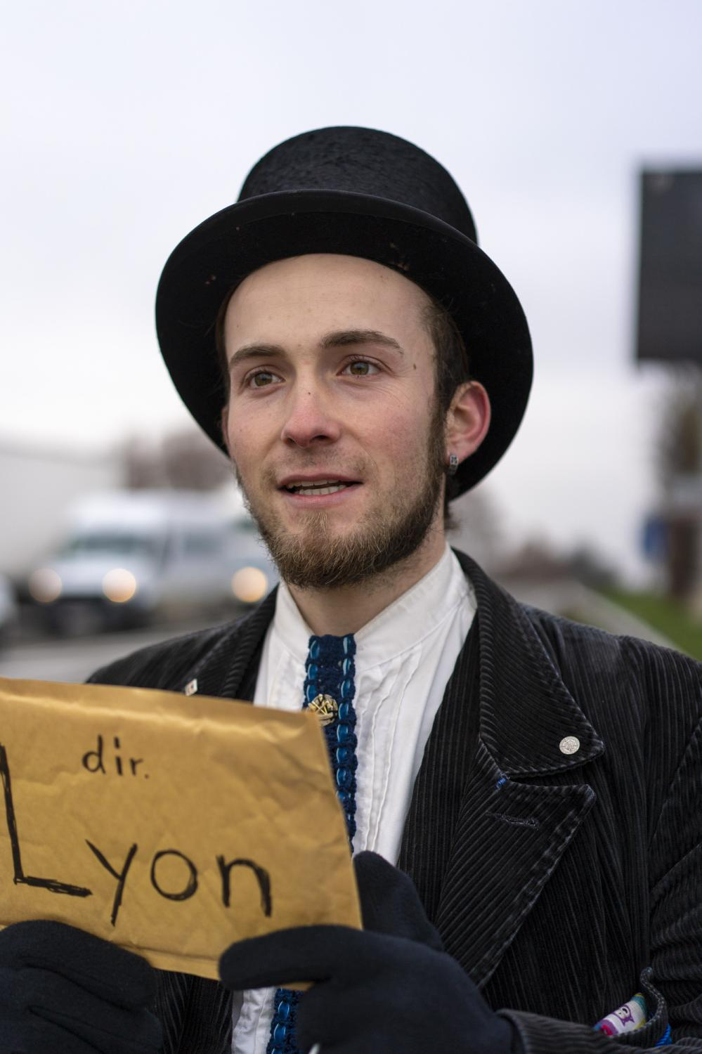 """Matthias holds a sign reading """"Direction of Lyon"""", to show drivers as he hitch-hikes on the driveway towards the highway of Strasbourg, France, on December 2, 2020. After walking to the outskirts of the city and standing on the right driveway, no car stopped for a couple of hours and a different approach was agreed: after a break in the adjacent shopping mall to warm up, the two travellers went to approach car drivers directly at a nearby gas station."""