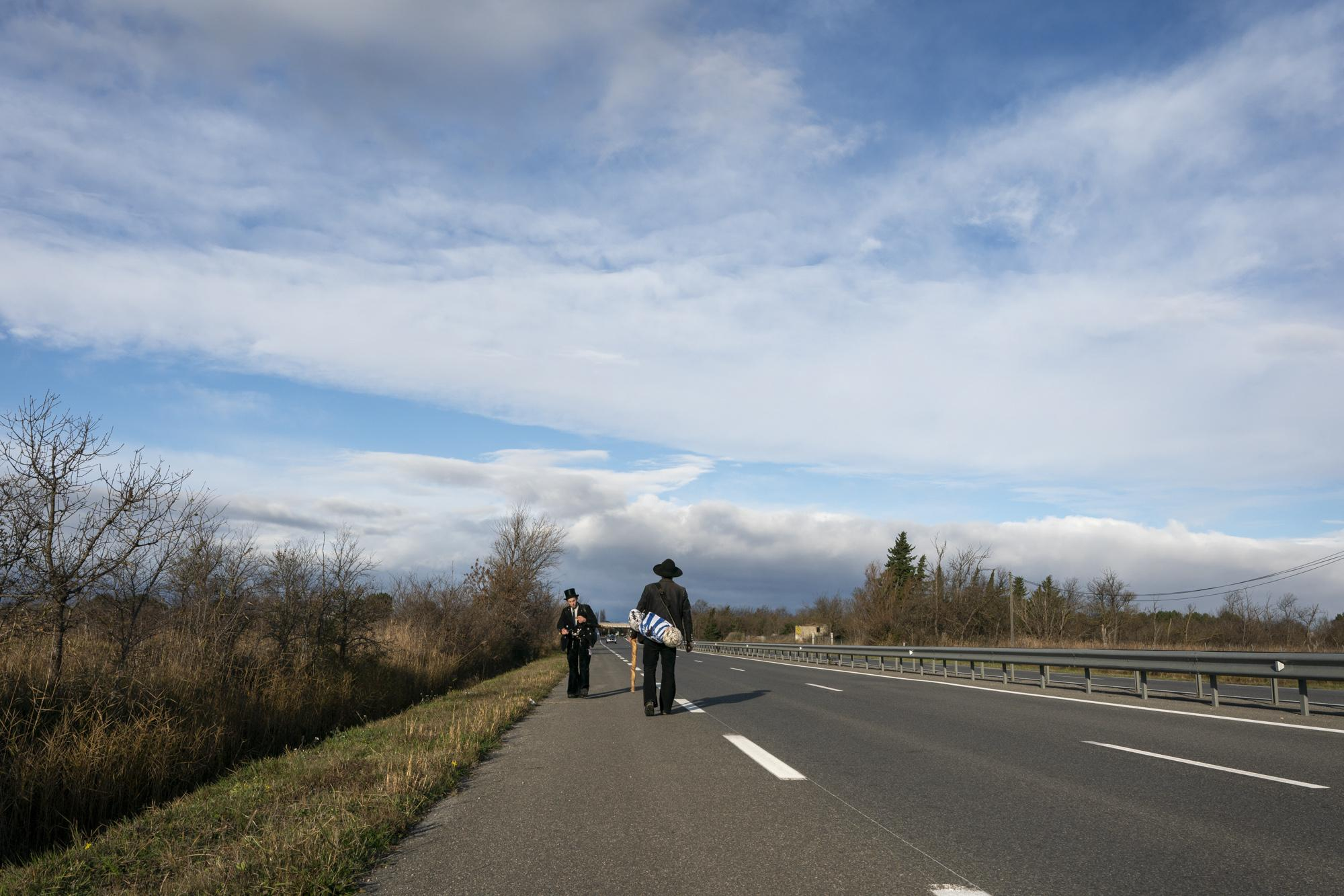 Matthias (L) and Ben walk along the empty road from Narbonne to Gruissan as they aim to reach the Mediterranean sea and watch out for a car to hitch-hike, in Narbonne, on December 6, 2020.