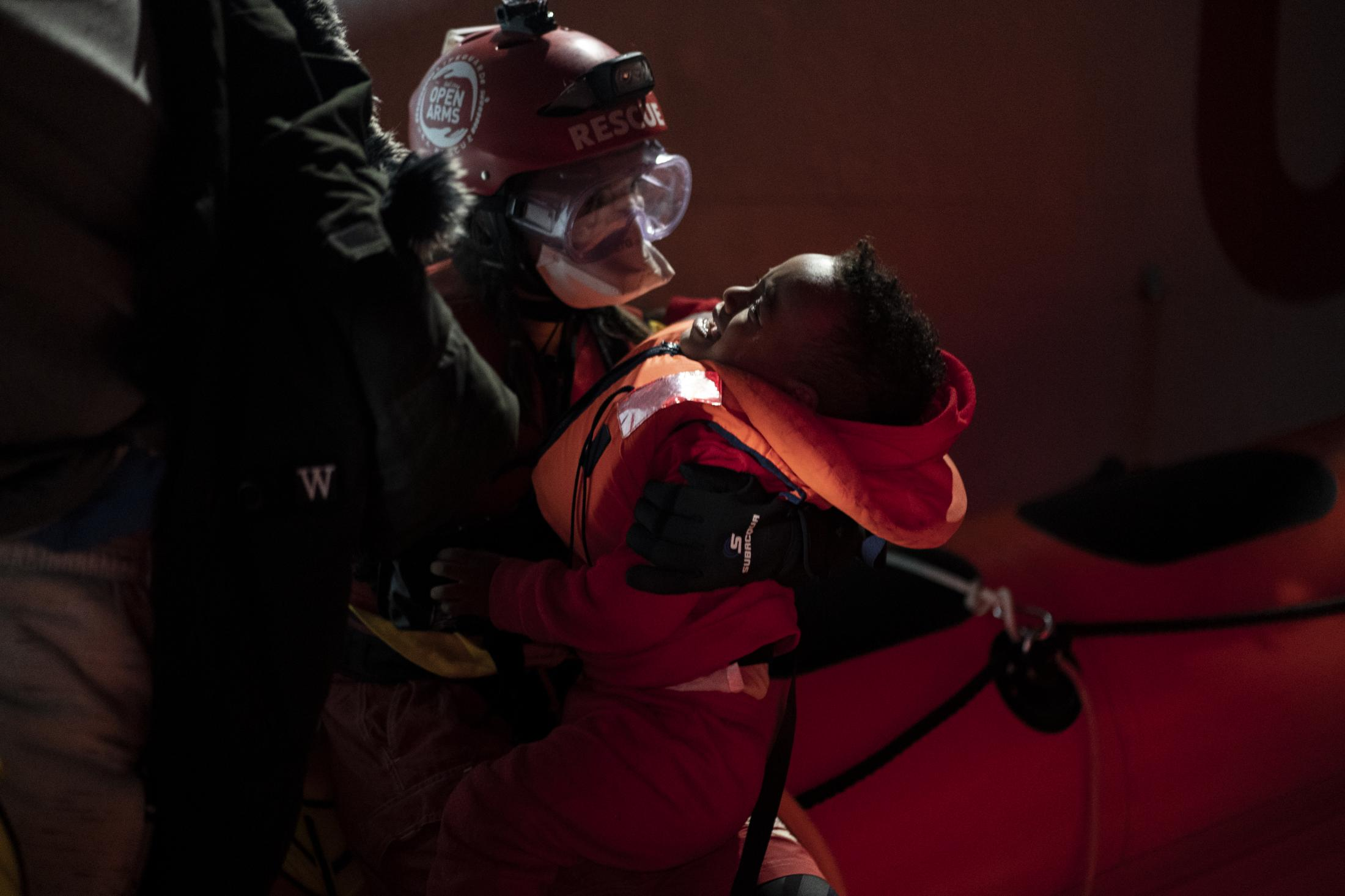 A baby is rescued by aid workers of the Spanish NGO Open Arms, after being located sailing adrift on an overcrowded wooden boat in the Mediterranean sea, about 85 miles north of Libya, on Thursday, Dec. 31, 2020. (AP Photo/Joan Mateu)