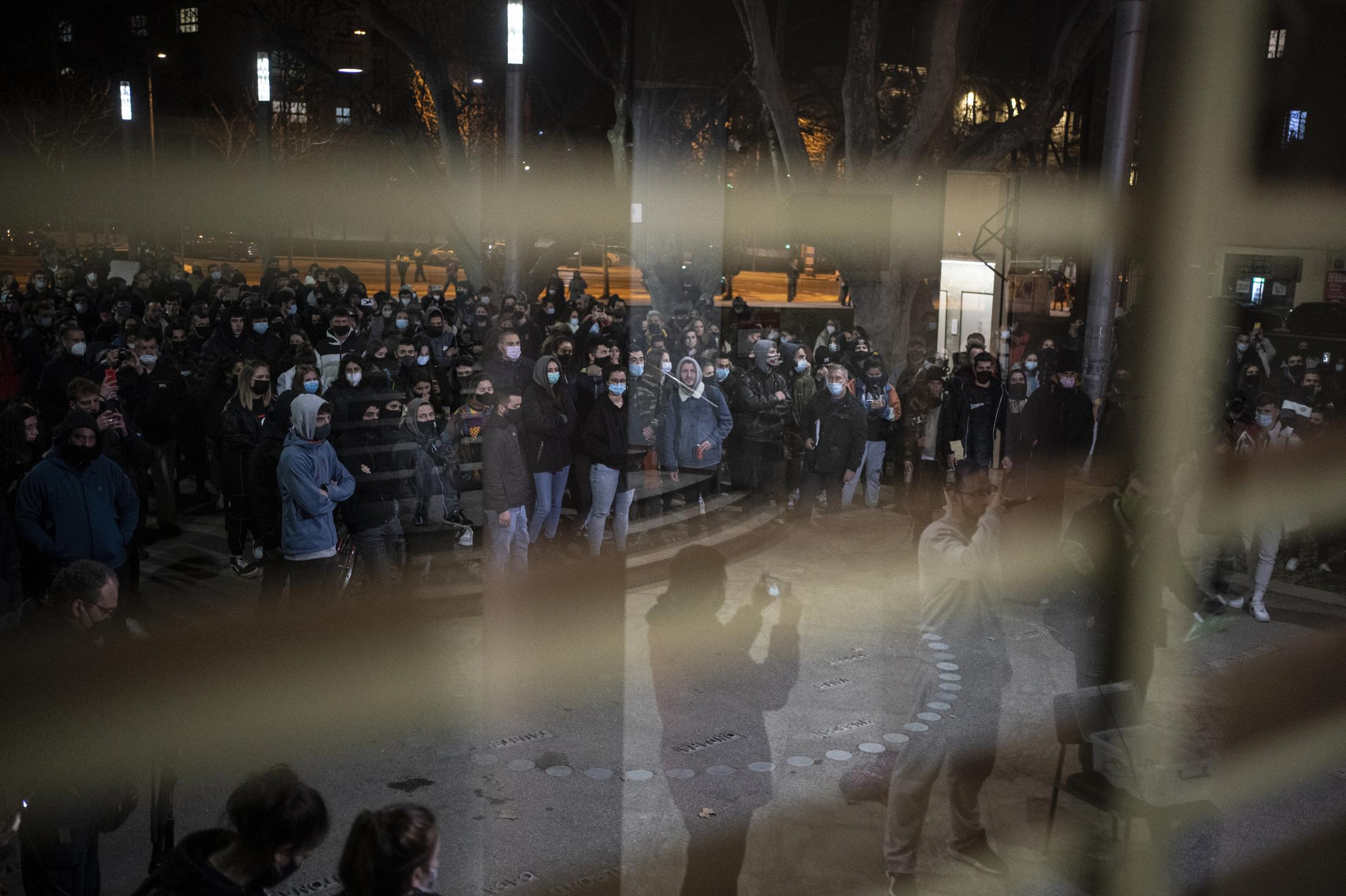 Rap singer Pablo Hasel, 32, is seen reflected on a window, bottom right, as he speeches at students gathered outside the University of Lleida, Spain, Monday, Feb. 15, 2021. A rapper in Spain and dozens of his supporters have locked themselves inside a university building in the artist's latest attempt to avoid a prison sentence for insulting the monarchy and praising terrorism. (AP Photo/Joan Mateu)
