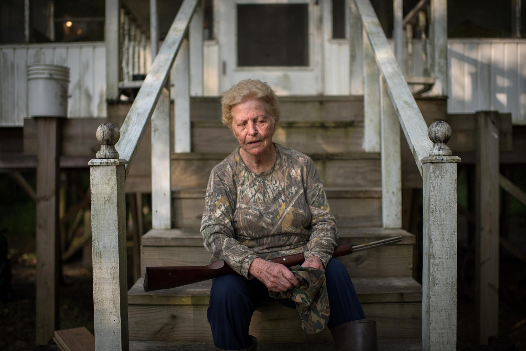 Squirrel hunter Annie Mendoza, 85, poses for a portrait outside her hunting cabin in Bayou Sorrel, Louisiana.