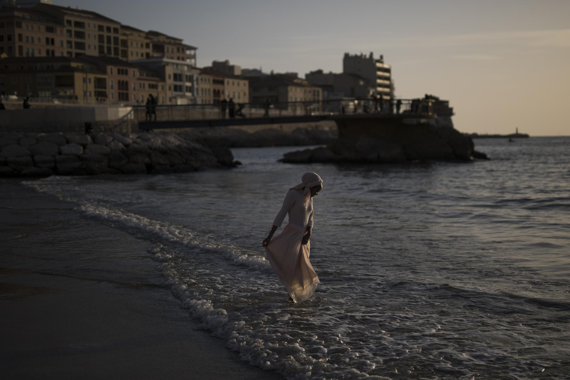 A woman dips her feet in the sea before curfew at Marseille�s Plage des Catalans, southern France, Sunday, Feb. 28, 2021. (AP Photo/Daniel Cole)