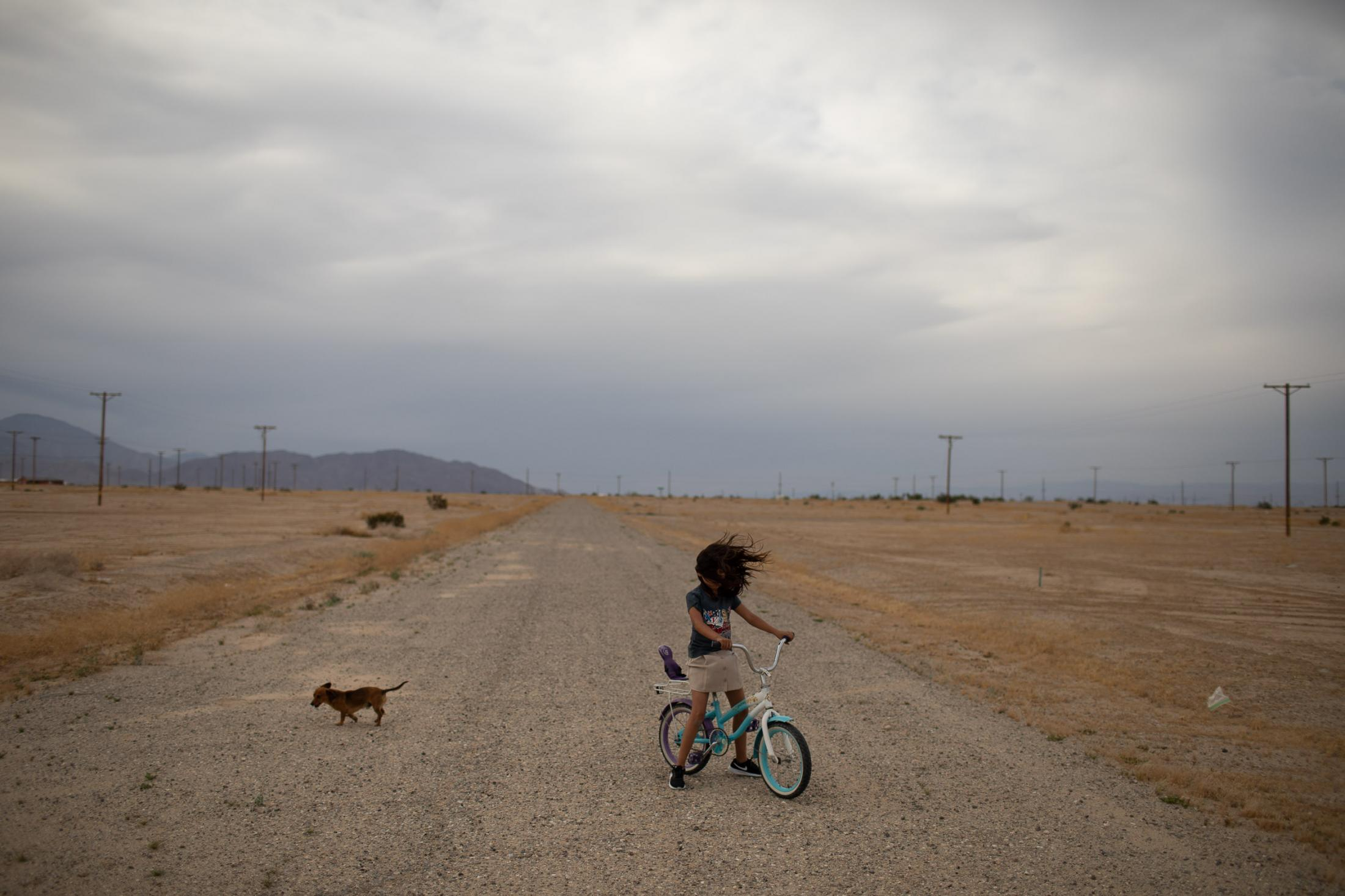 Lizzette is playing on her bicycle as strong winds are blowing across her neighborhood in Salton City.