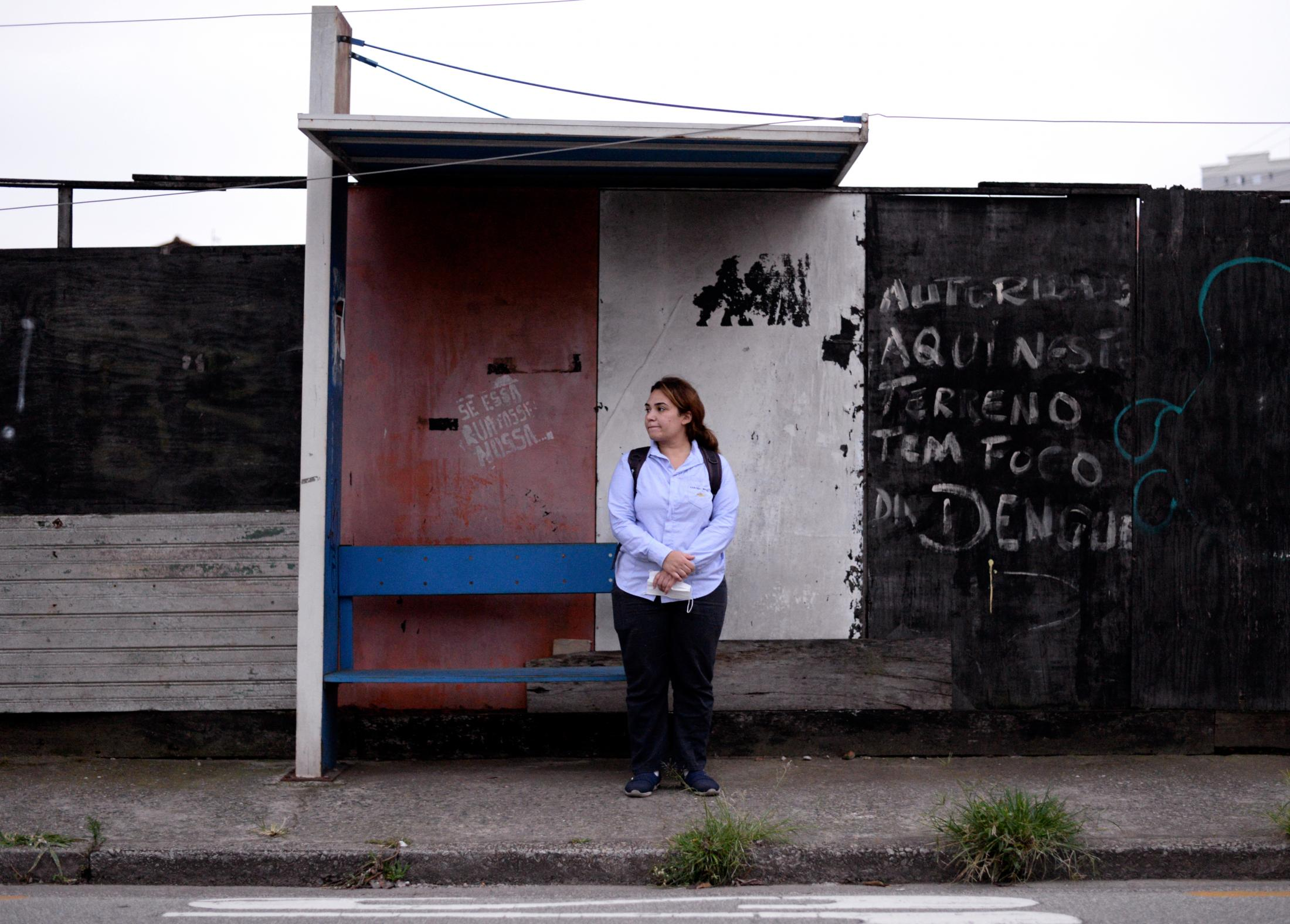 Rama AlOmari waits for her work's private bus on Friday, Dec. 11, 2020, in Santo Andre, Sao Paulo State, Brazil. AlOmari works at General Motors, in a mask production factory for all Latin America General Motors headquarters. She goes to work at 5 a.m.
