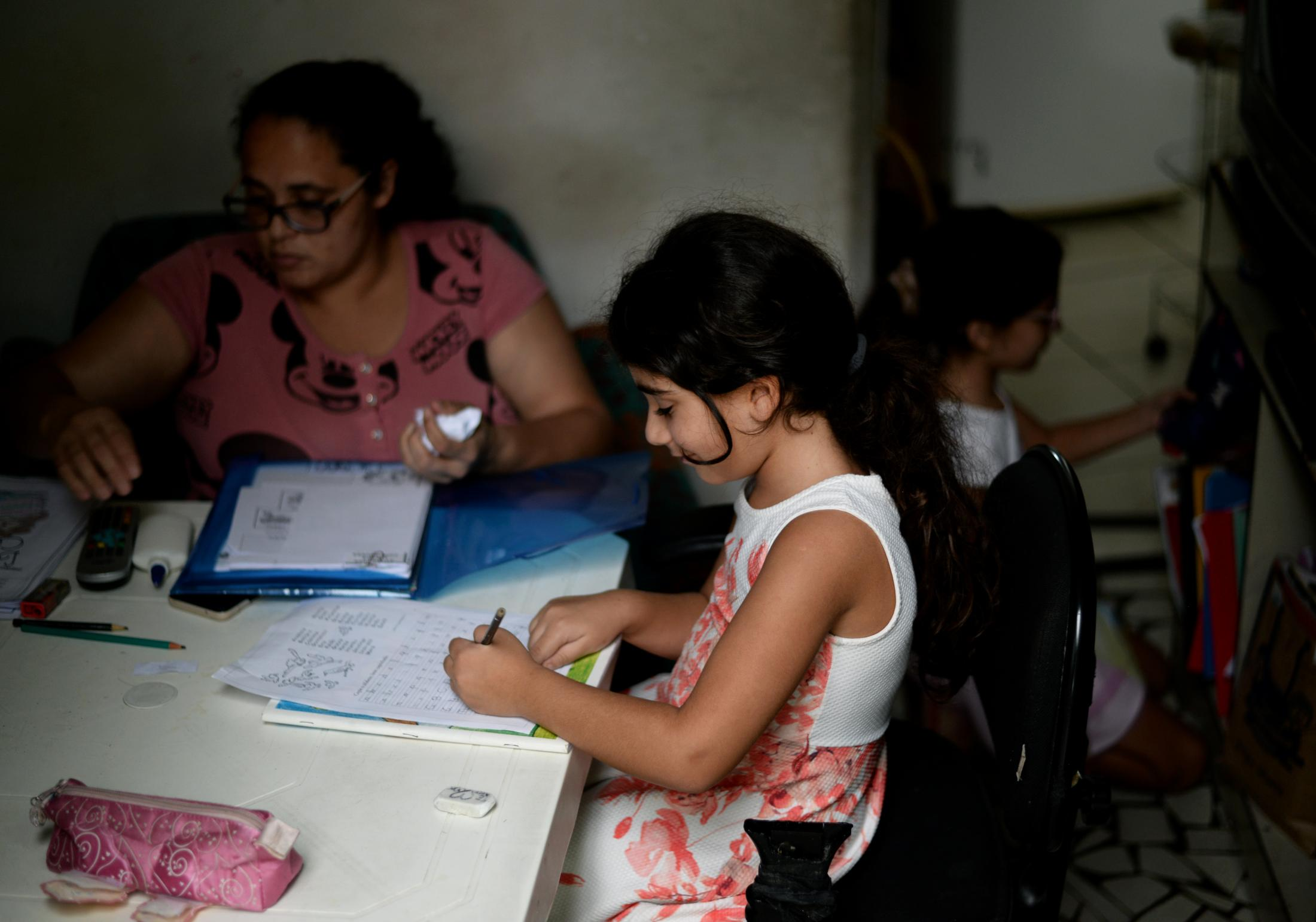 Celin Ibrahim, 7, center, finishes her daily homework while her teacher Carina Aparecida Rosa, left, and her sister Lamar organize their materials on Thursday, Dec. 10, 2020, in Santo Andre, Sao Paulo State, Brazil. Rosa helps by taking care of the sisters while their mother is at work. Rosa says that the girls are obedient when doing their schoolwork.
