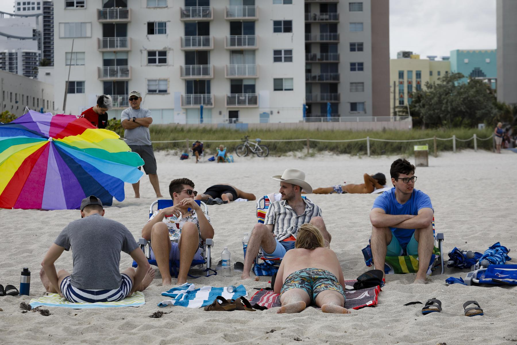 People sit on the beach during Spring Break in Miami Beach, Florida, U.S., on Saturday, March 6, 2021. Photographer: Eva Marie Uzcategui/Bloomberg