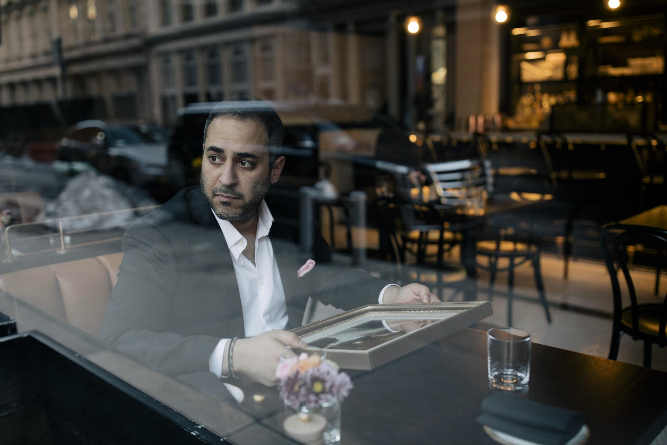 New York City, New York — February 24, 2021: Andreas Koutsoudakis Jr., 36, a restaurant lawyer at Koutsoudakis & Lakovou Law Group and Owner of TriBeCa's Kitchen, sits in a booth with a portrait of his father, Andreas Koutsoudakis Sr. who died of Covid-19 in March, before the evening dinner service in late February. As the impact of the COVID-19 pandemic rolls into February, many residents of New York City continue the exhausting effort to navigate the many complexities the pandemic has brought to their lives and businesses. CREDIT: José A. Alvarado Jr. for The Wall Street Journal