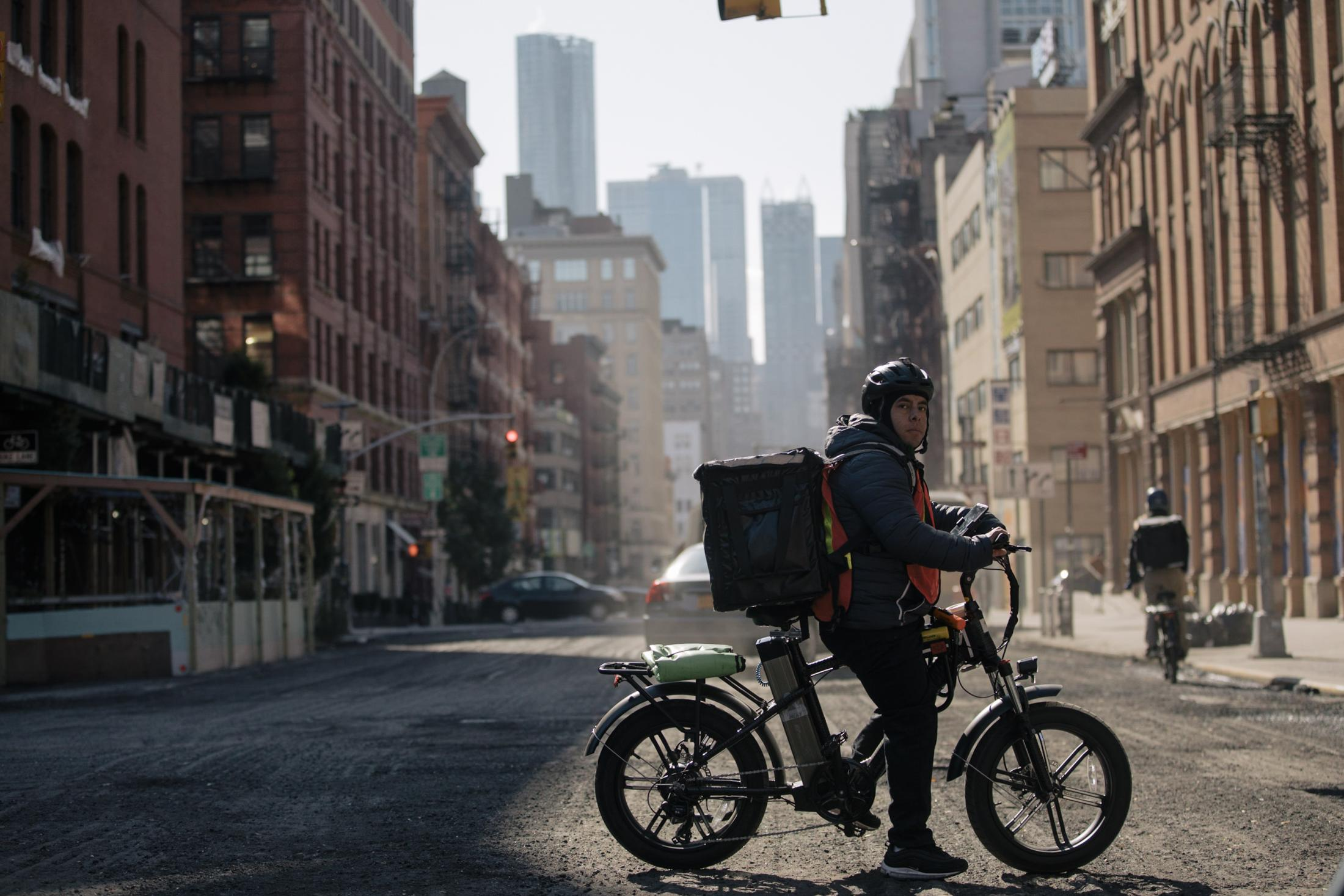 New York City, New York — October 31, 2020: As the morning sun makes it way over Manhattan, Sergio Ajche attempts to keep warm by moving about on Lafayette Street and Broom Street near Lt. Petrosino Square as he waits for deliveries. Since early March, the complexities of COVID-19 has shed light on the various obstacles in the gig economy, from wage theft to bare-bones wages, leading many to voice their frustrations to the growing mistreatment of this invisible army. CREDIT: José A. Alvarado Jr. for The New York Times