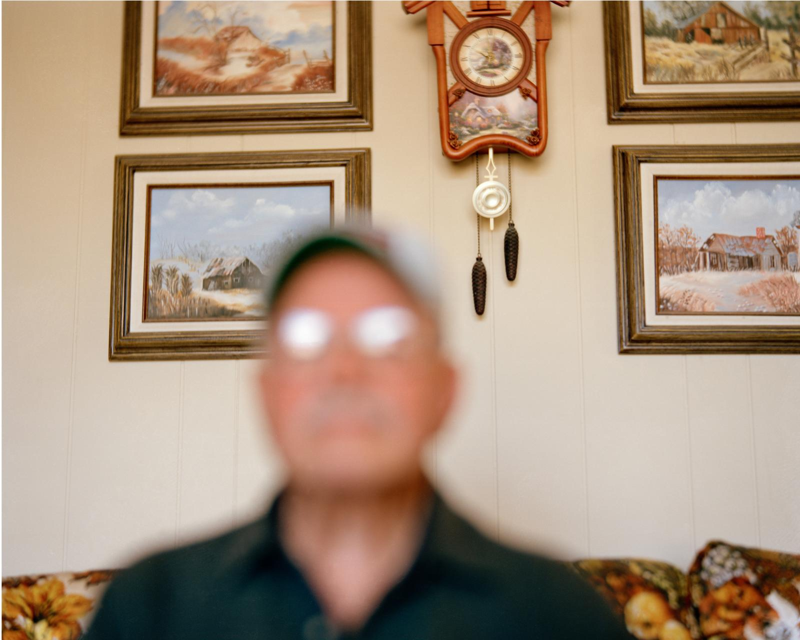 """San Antonio, NM, Tiburcio Padilla born January 20, 1933, witnessed the Trinity Bomb test as a 12-year-old child. - Photographed at home in San Antonio, NM He and three of his siblings grew up to be sterile. Tiburcio Padilla, 83, looks out his window while recalling the day on July 16, 1945 when as a boy he witnessed the first atomic bomb blast. """"All of a sudden we heard that boom and we saw that mushroom cloud come up. The ground just shook all over. We didn't know what happened."""" The atomic age had been born thirty miles away in the Jornado del Muerto desert. The Trinity test marked the triumph of the Manhattan Project and paved the way for the quick assembly of nuclear weapons, which were dropped August 6 and August 9 on Hiroshima and Nagasaki, killing and maiming hundreds of thousands. Residents living around the Trinity test site were never monitored or studied for health impacts, unlike down winders in Nevada and Utah. In 2014, the National Cancer Institute began a survey, a full 69 years after the event. Padilla grew up sterile, as did another brother and two of his sisters. Four out of twelve children in his family were unable to conceive. He wonders if his proximity to the test and resulting radiation rendered him infertile. The Trinity test site is open to the public two days a year. It still emits high levels or radiation."""