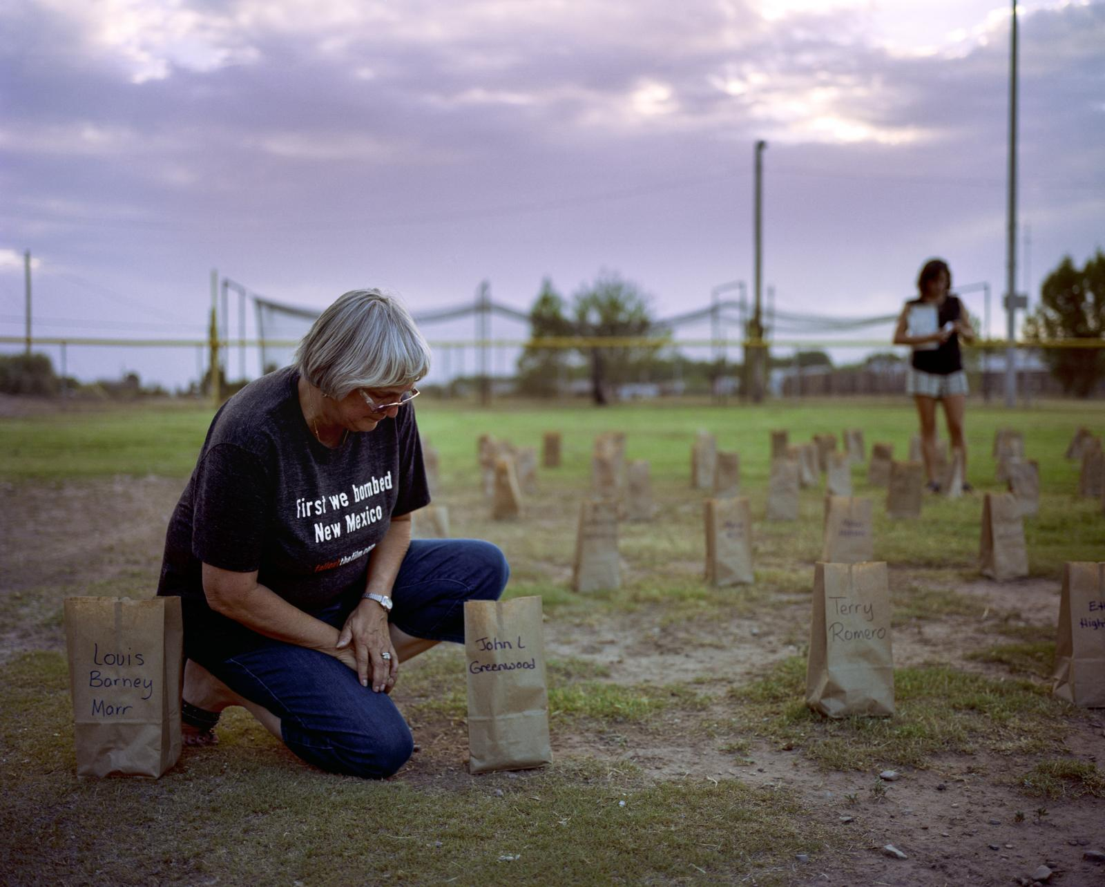 Laura Greenwood, Tularosa, New Mexico, USA, July 16, 2016  Laura Greenwood places a candle in a lantern for her husband John Greenwood who died in 2012. He was the12th member of his family to die of cancer. He grew up in Alamogordo, New Mexico, is 75 miles from the Trinity Site.  Each year, Laura drives from Texas for the July 16 candlelight vigil held in Tularosa to memorialize the people they have lost to cancer and other illnesses related to radiation exposure.