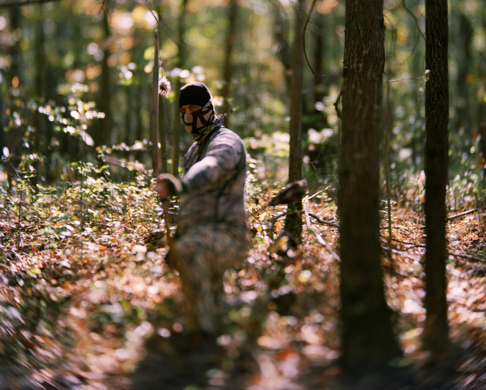 Hunter, Big Oakes Wildlife Refuge, Madison, Indiana, October 22, 2016  A traditional bow hunter poses in the woods during deer hunting weekend at the Big Oakes Wildlife Refuge. Big Oakes lies on the former Jefferson Proving Ground, which operated from 1941 – 1995 as a training ground for US Army weapons. More than 24 million rounds were fired on the grounds. At the height of its operation – the Korean War - 175,000 rounds were fired per month. From 1984-1994, JPG test fired 100,000 kg [220,462 lbs.] of tank penetrator rounds containing depleted uranium (DU). Despite some cleanup, the area still contains 154,324 lbs.] of DU and 1.5 million rounds of unexploded ordinance (UXO) In 2000, the Department of Defense worked out an arrangement with the US Fish and Wildlife Service which took over stewardship of the contaminated landscape and established the Big Oaks Wildlife Refuge on 51, 000 acres of the former proving ground. The land is too contaminated with DU and littered with so much unexploded ordnance that it can never be developed commercially or developed for human habitation.  And so only a few areas have been cleared for human leisure activities and a few weekends a year, hunters are allowed on certain parcels. The landscape presents a paradox. It looks pristine but only because it's so contaminated that much of it is a closed zone.
