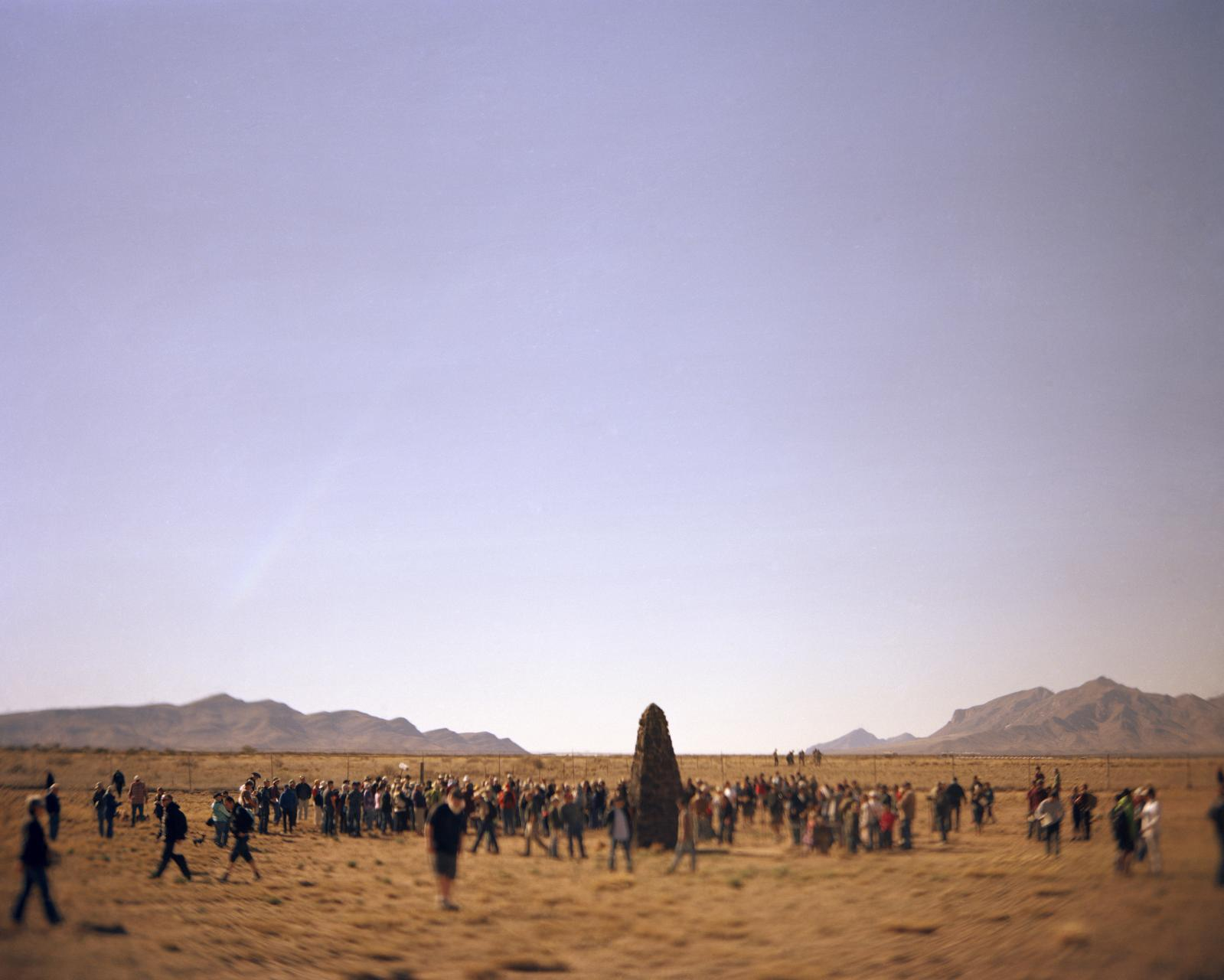 Trinity site, White Sands Missile Range, New Mexico, USA, April 2, 2016  The public gathers around the obelisk monument to the first atomic bomb detonation July 16, 1945.  Radiation spread at least as far as Indiana, and the Wabash River, where Kodak Film Company sourced water for its paper mill to package its film. Customers ended up complaining that their film was fogged and the company secured a pledge form the Atomic Energy Commission to provide Kodak with dates and fallout patterns for future tests, thereby notifying corporate America, but not the American people, of the radiation risk. Today the site is a closed military zone opened only two days a year to public. Higher than normal radiation levels are still detected and residents of New Mexico claim that they have suffered cancer for generations as a result of the test but have never been compensated.