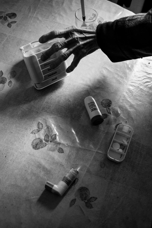 une main tendu vers le pilulier.