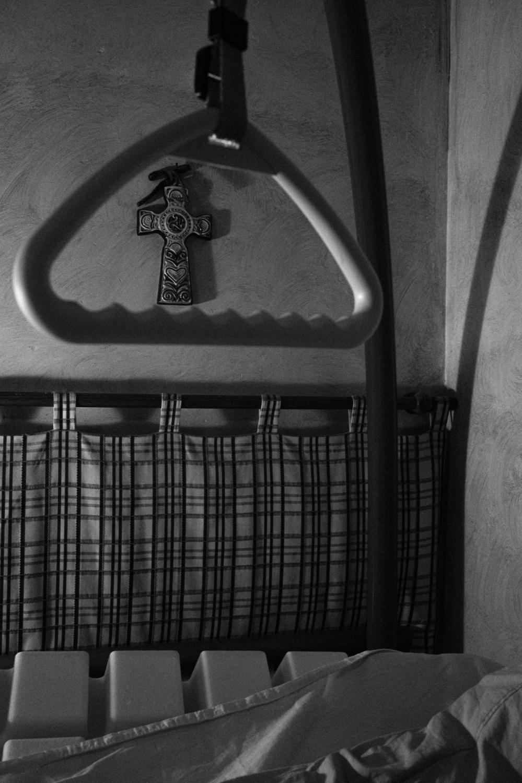 Un lit médicalisé surplombé d'une croix.