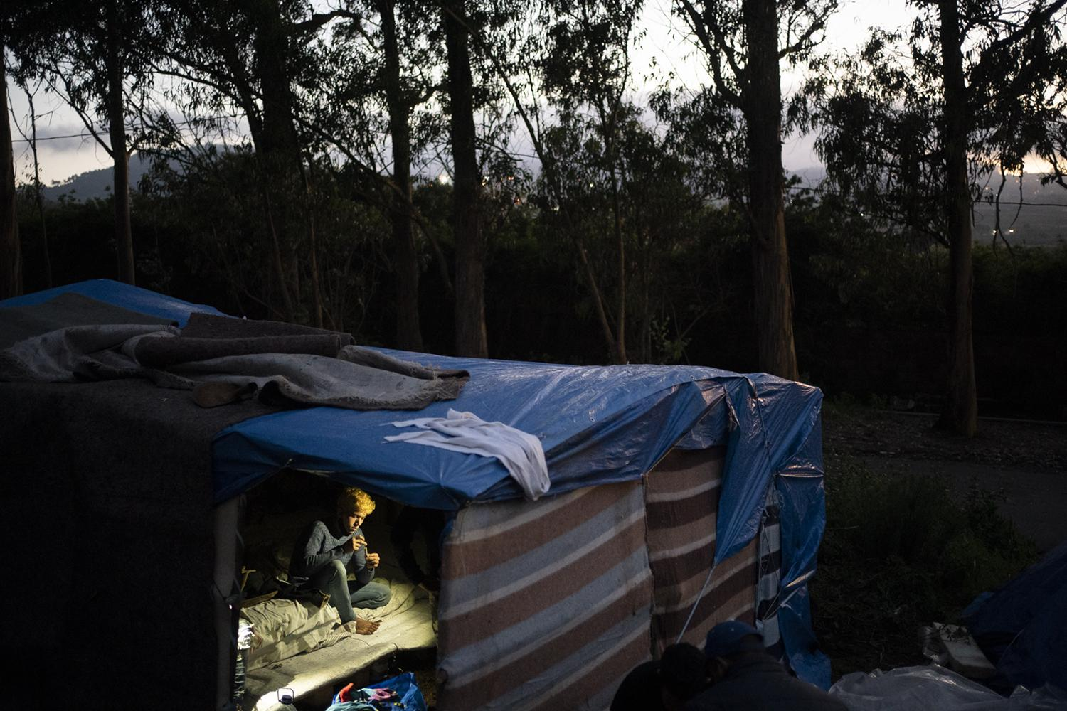 Ayoub, 22, from Morocco, rests in Las Raices camp in San Cristobal de la Laguna, in the Canary Island of Tenerife, Spain, Wednesday, March 17, 2021. Several thousand migrants have arrived on the Spanish archipelago in the first months of 2021. Due to the terrible living conditions and the poor quality of food and water at the Las Raices camp, some migrants have decided to leave the camp and sleep in shacks in a nearby forest instead. (AP Photo/Joan Mateu)