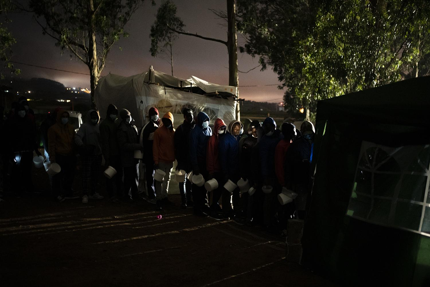Migrants queue up to receive food in Las Raices camp in San Cristobal de la Laguna, in the Canary Island of Tenerife, Spain, Wednesday, March 17, 2021. AP Photo/Joan Mateu)