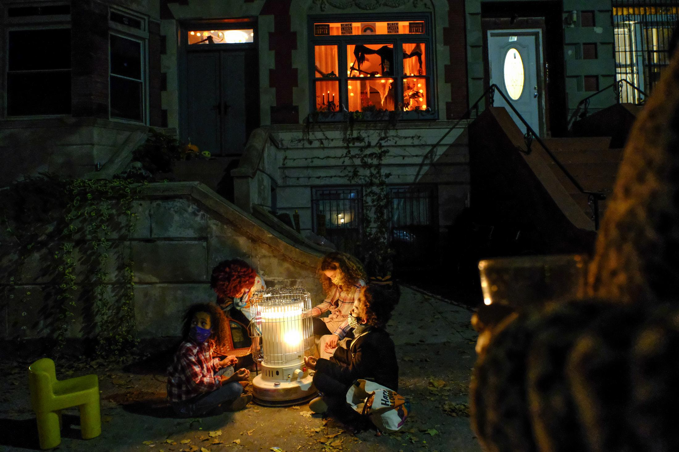 October 31, 2020: After a long evening of trick or treating on our block, the kids warm themselves at Sam and Micaela's outdoor heater. The adults look on and sip wine.