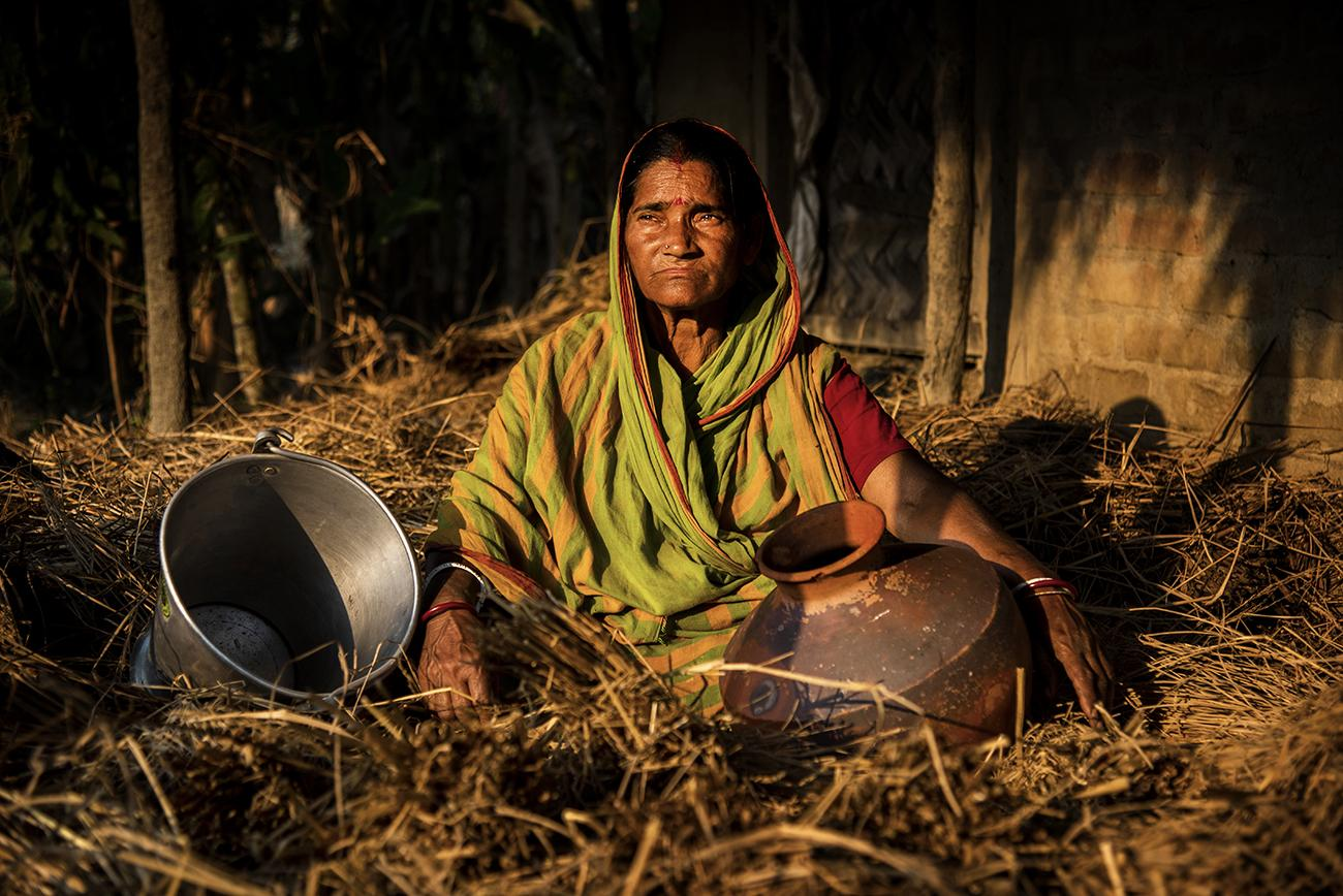 A symbolic portrait of Gita Maity sitting in front of her house with empty pots, a 63 years woman in Madhab Nagar area of Pathar Pratima under South 24 Parganas district of West Bengal, India.