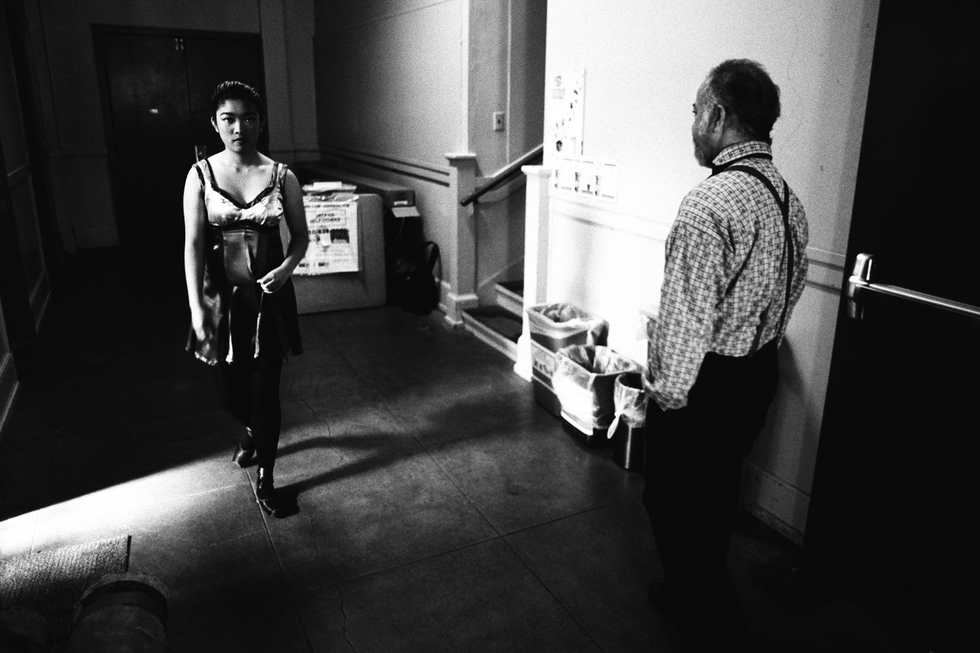 A young dancer from the Alameda Civic Ballet passes an older dancer from the Barbary Coast Cloggers, backstage at Kofman Theatre.