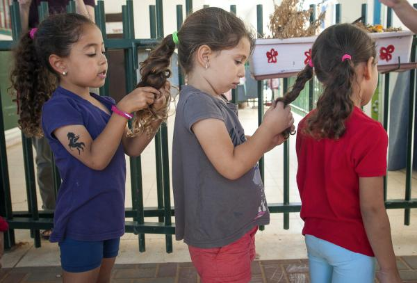 Wadi Ara Kindergarden students Lor Sawalha, Aline Kitane, Duna Gawi getting ready to go out into the main playground.
