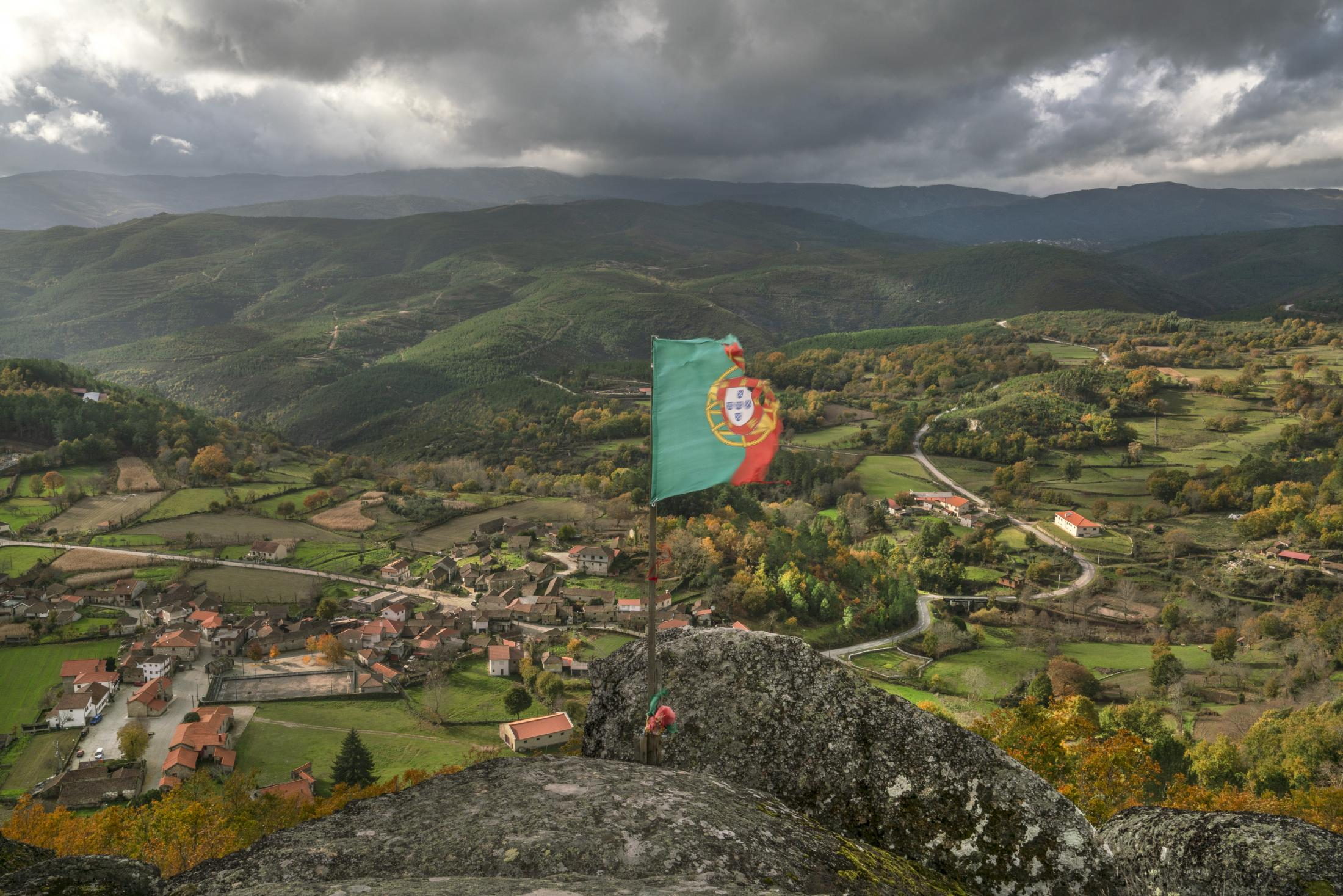 Portuguese flag flies on a hill overlooking the village of Covas do Barroso, in the Barroso region of Portugal. The mountains behind the village contain a large lithium vein that the Portuguese government would like to see explored as part of its objective to turn the country into a manufacturing hub for electric car batteries. The planned open-pit mine would be less than 500 meters from the center of the village and would require changing the course of the river that crosses the village, threatening the springs that irrigate the fields of most local farmers
