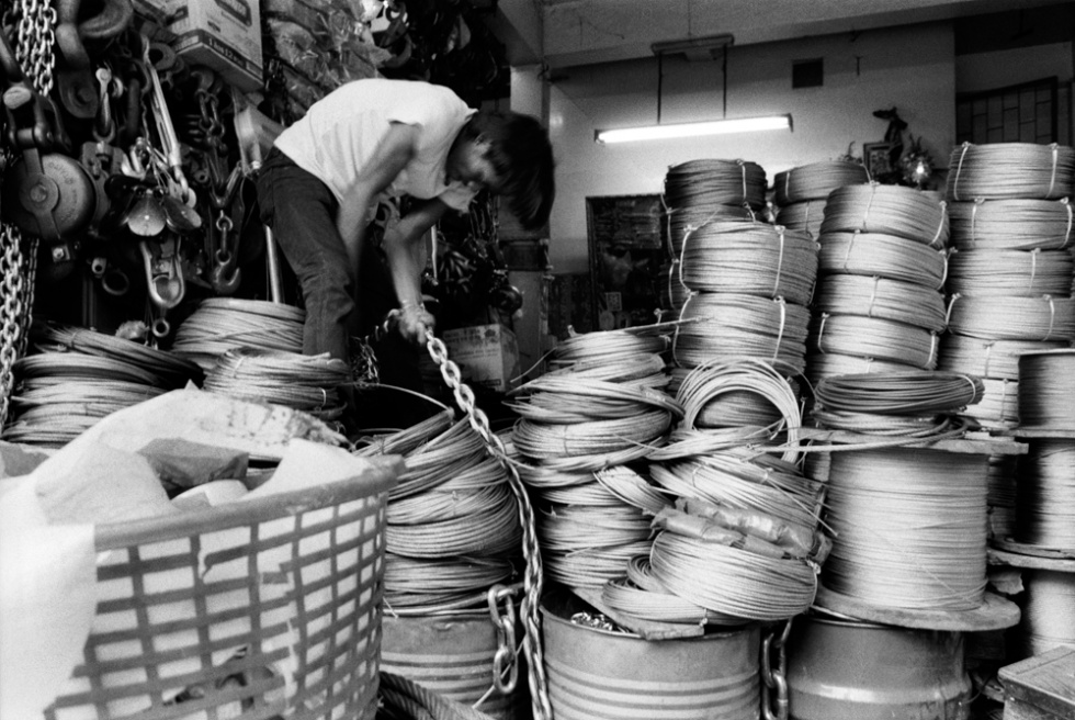 Man arranging steel cables. Nakhon Kasem market, China Town, Bangkok, Thailand.