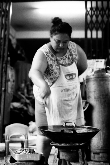 Woman cooking on the door-step of her house. Nakhon Kasem market, china town, Bangkok, Thailand.