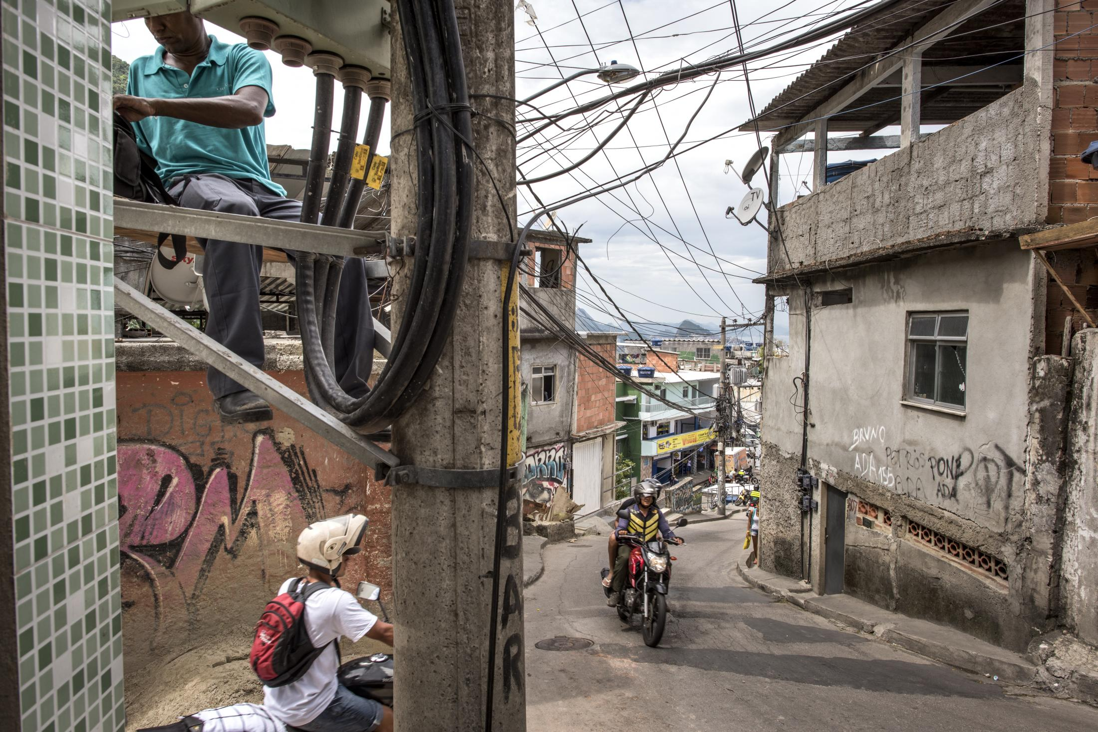 Worker from Rio's eletricty company work on a lamp post along the main road of Vidigal