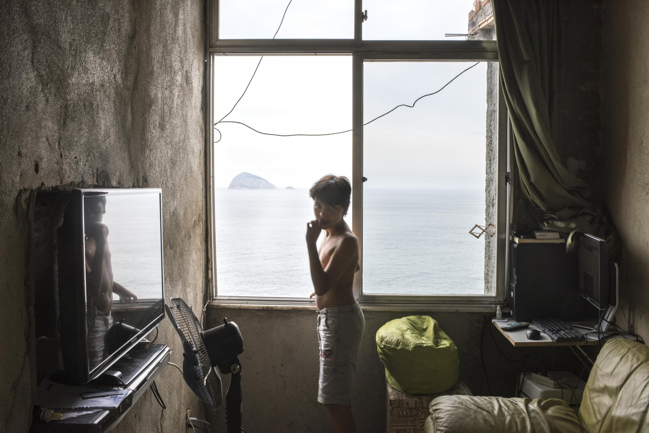 The son of Walmar Luiz, a community organizer in Vidigal who also works as a location scout for film productions, in the living room of their home overlooking the ocean
