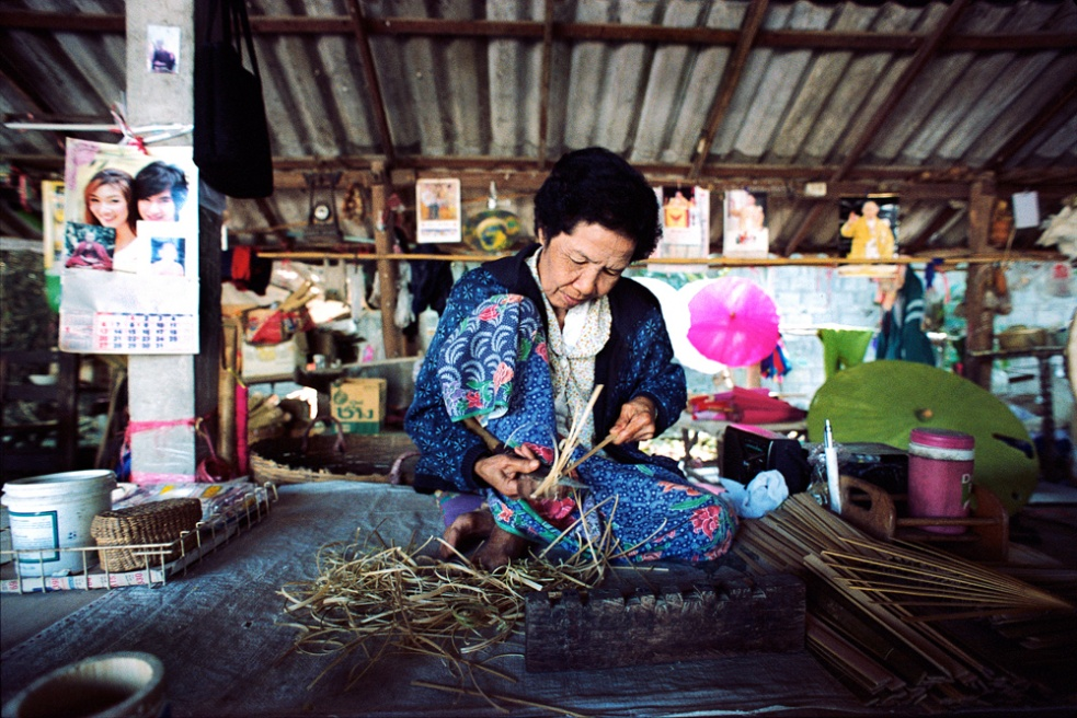 Woman making straw umbrellas. Chiang Mai, Thailand.