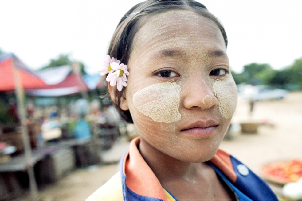 Girl with sunscreen and flower. Nyaung u market, Bagan, Myanmar.