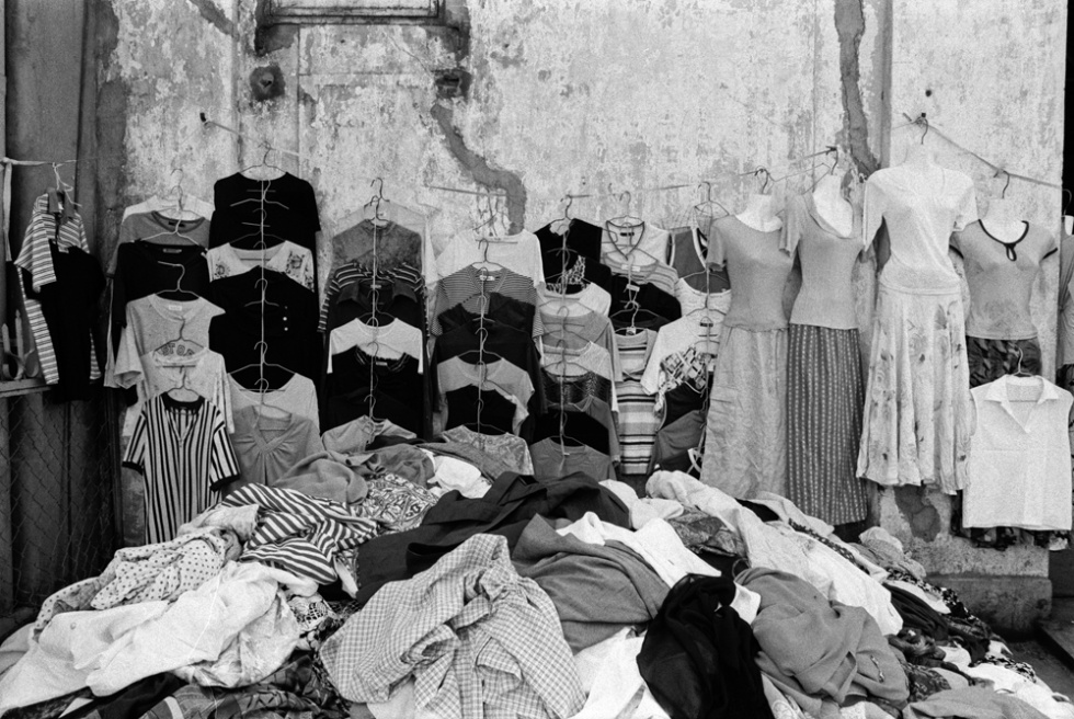 Old and new clothing displayed on the wall of a colonial house. Psah Thmay central market, Phnom Penh, Cambodia.