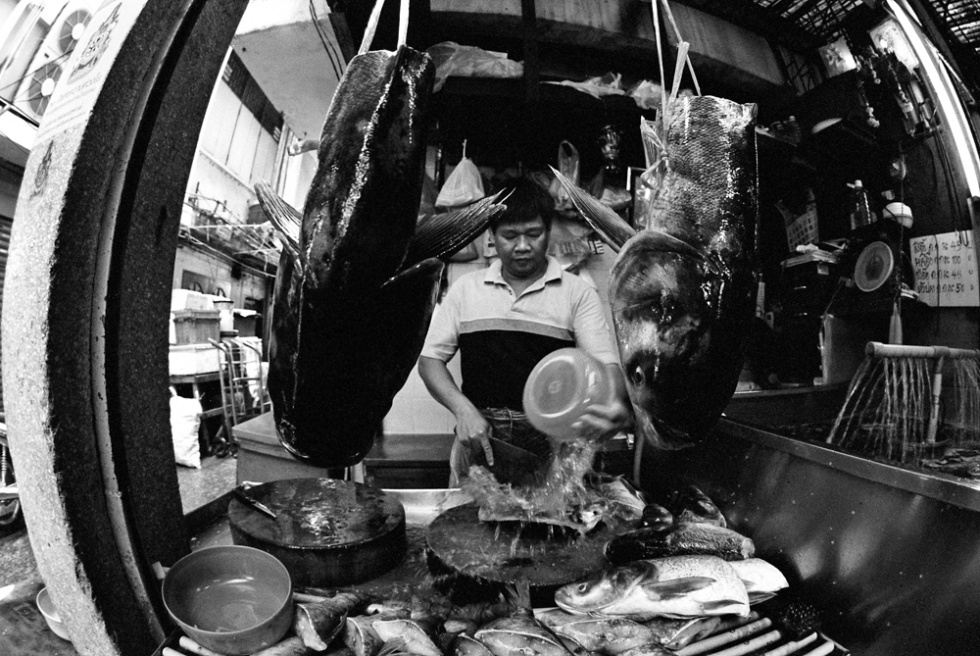 Man gutting fish. China Town, Bangkok, Thailand.