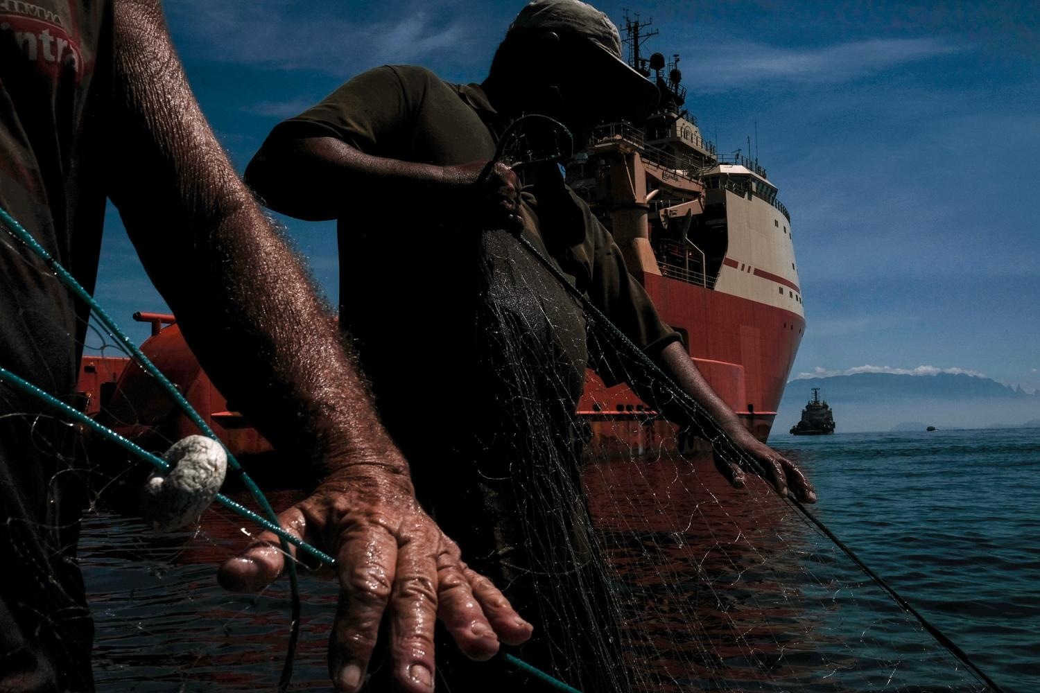 The oil vessels are dotted all over the bay. The fish tend to hide under them, but even then they're lucky to get a good catch. Artesanal fishermen use time-tested methods but it's still back-breaking work hauling empty nets.