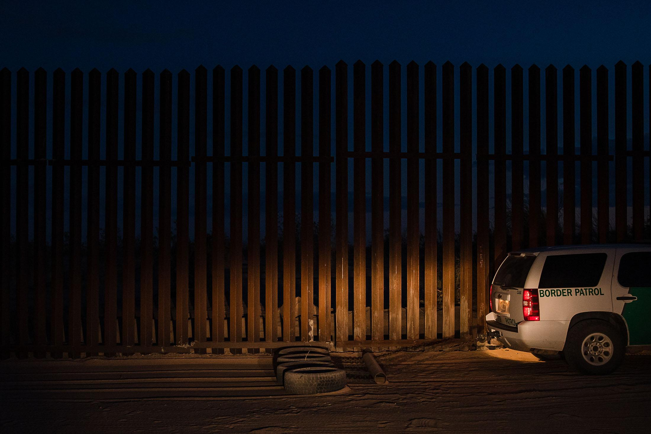 A Border Patrol agent drags tires behind his vehicle to smooth out the ground in front of the border wall, making it easier to recognize new footprints from migrants coming into the United States illegally in front of the section of the now repaired border wall that was breached in early March near the Gordon's Well exit just off Interstate 8.