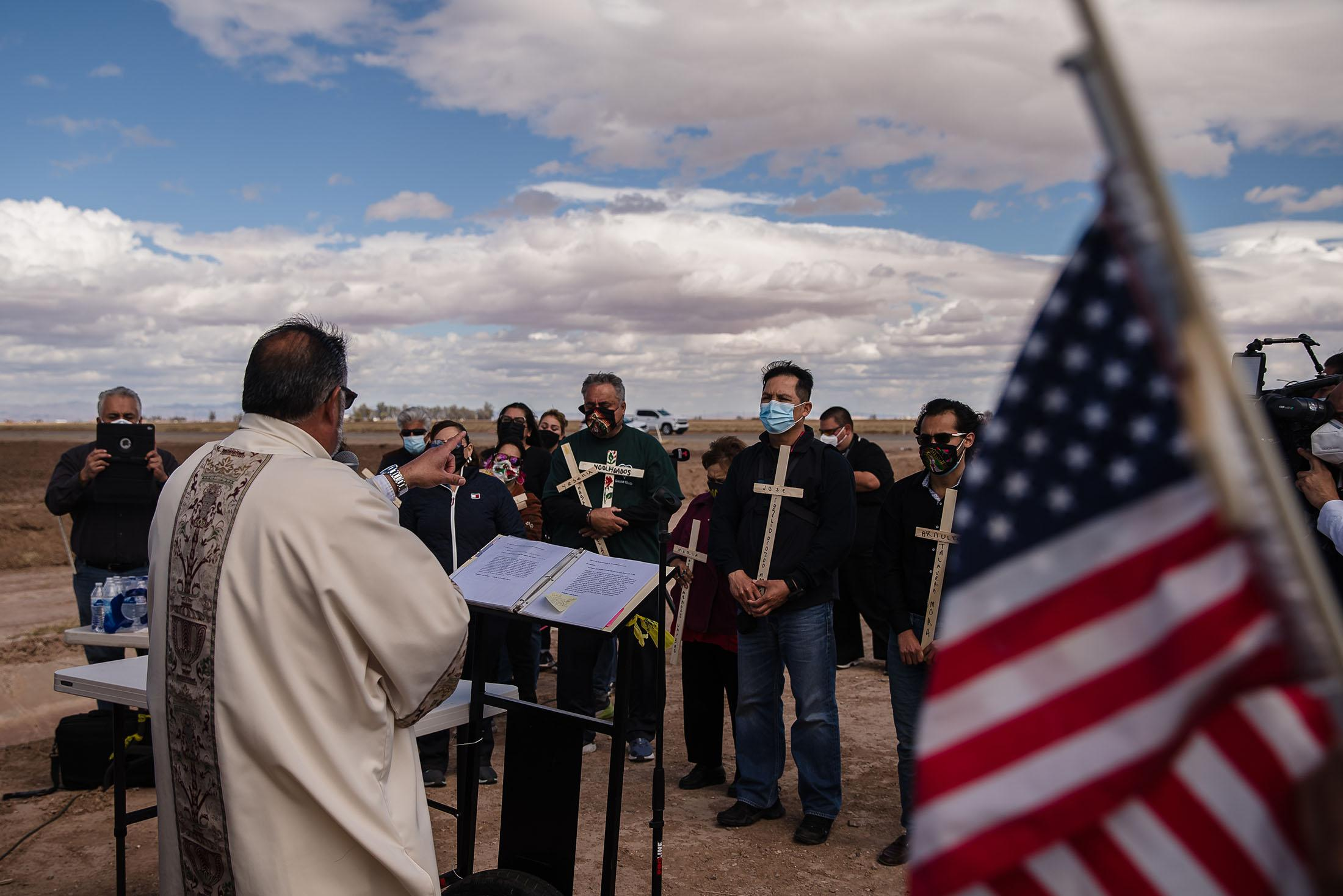Mourners holding crosses with the names of the13 undocumented immigrants who lost their lives, listen to Deacon Marcos Lopez (left) from Brawley Catholic on March 10, 2021 near the crash site.