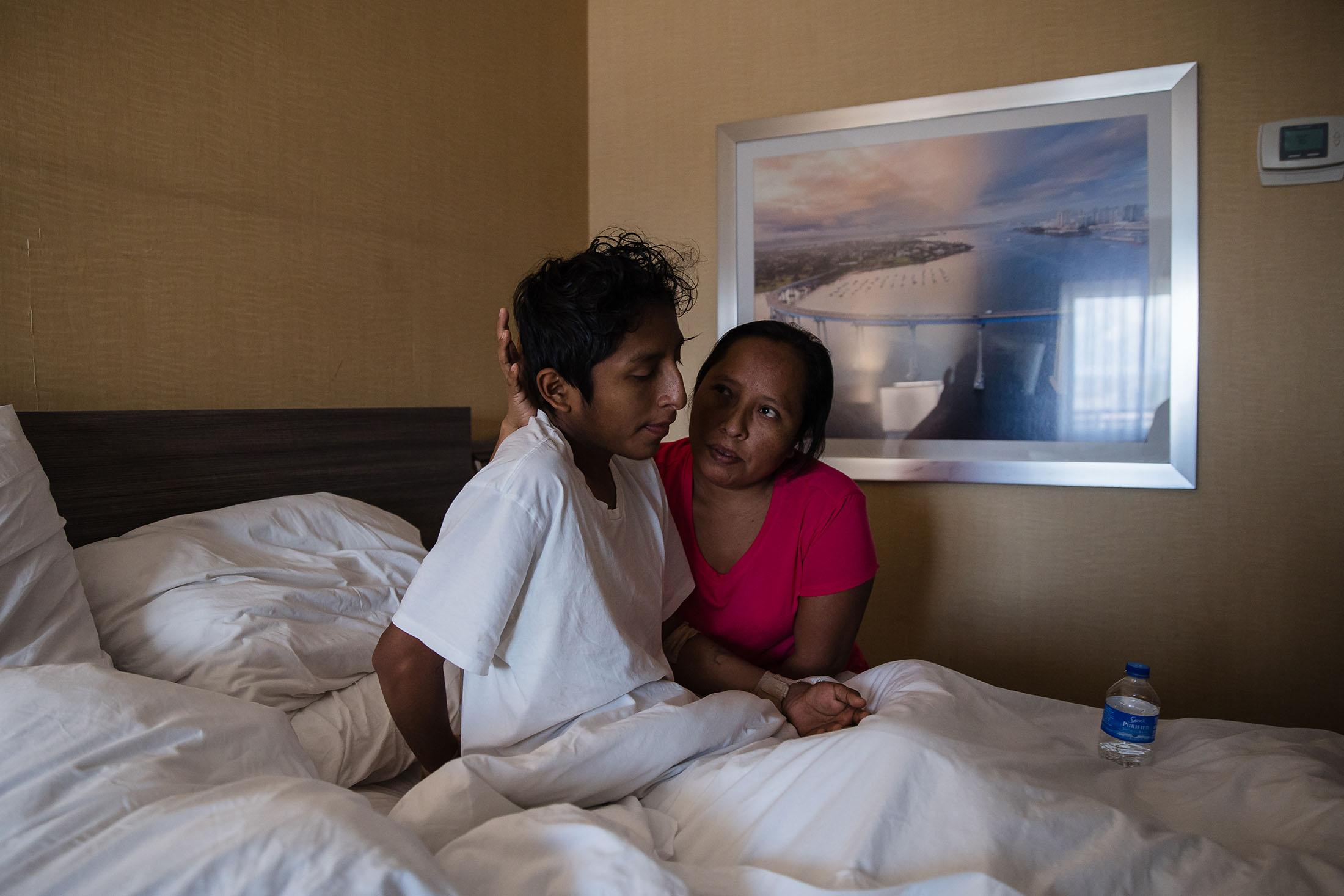 Maria Felix Martinez Gonzalez helps her son Jose Eduardo Martinez Gonzalez, 16 years old sit up in his hotel bed in San Diego, California on March, 11, 2021.