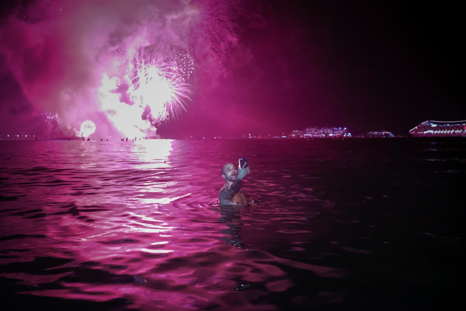 A man takes a selfie in front of fireworks at Copacabana beach during the 2018/2019 New Year's Eve celebrations, Rio de Janeiro, Brazil.