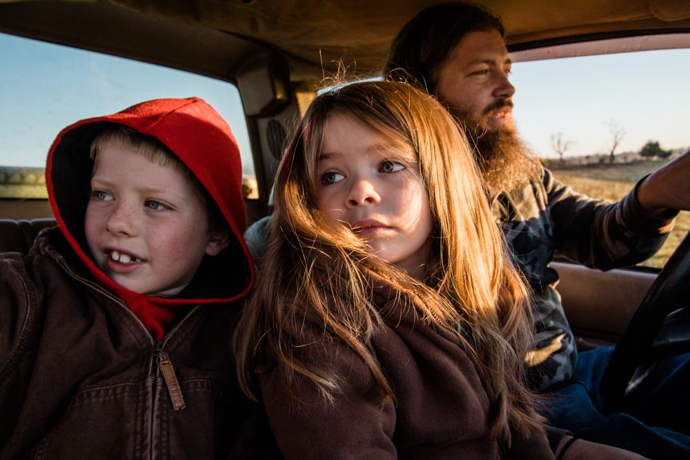 Brennen Moore, 9, and his sister, Briana, 4, ride with their father, Josh Moore, 36, to cut wood for the winter. The Montgomery County farm, C&J Cattle, has been in the Moore family for several generations.