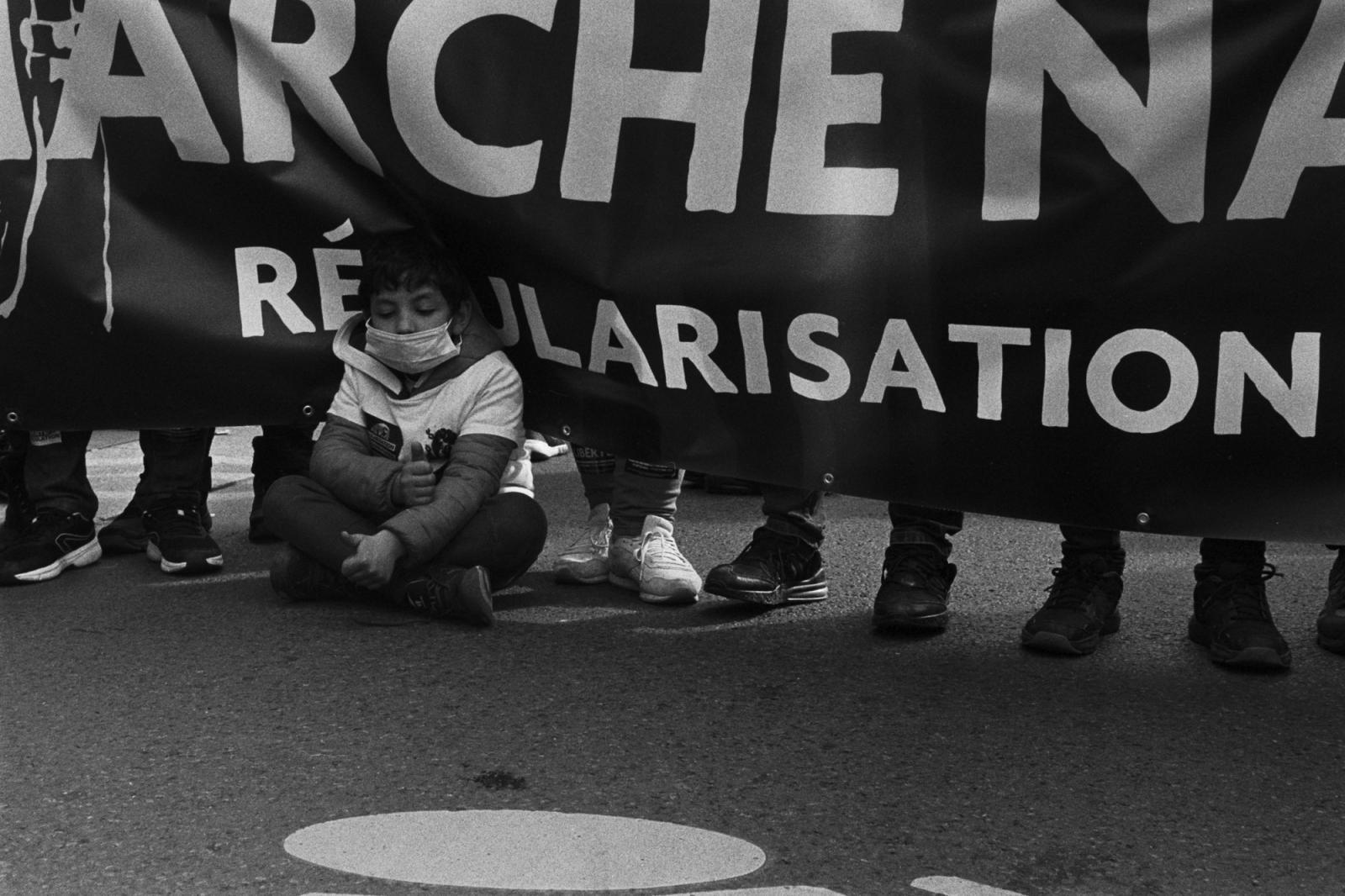 Manifestation des sans-papiers le samedi 17 Octobre 2020. Les manifestants viennent de la France entière. Ils se sont regroupés à Place de la République à 14h après leur longue marche qui a commencé le 19 Septembre 2020, il réclamé leurs régularisation .Un enfant assit sur la route à côté d'une banderole .