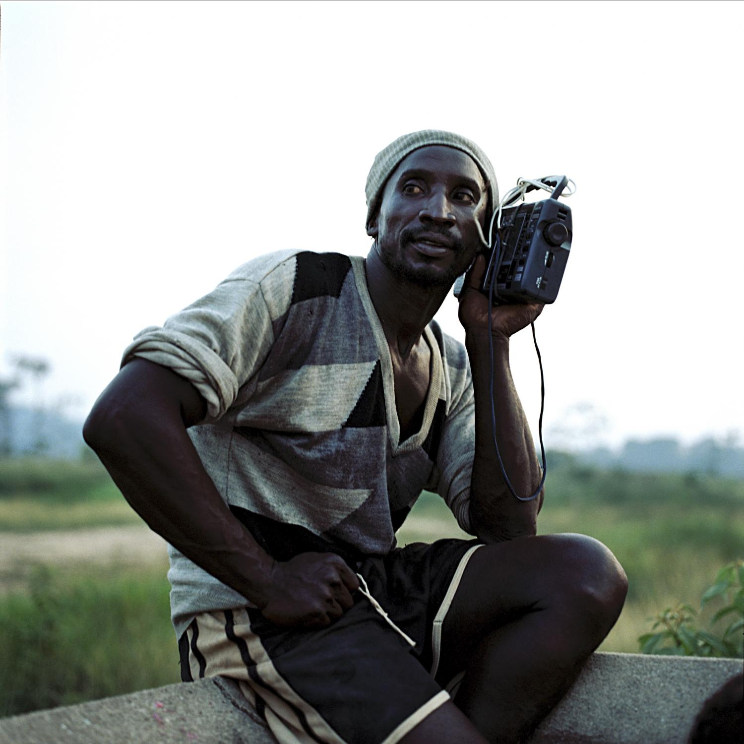 Miner listens to the radio while watching a soccer match at Vila Canopus. The village used to be the workers camp for a deactivated cassiterite mine operated by the French corporation Rhodia. A small community of miners lives in the infrastructure left behind by the company, making a living from mining the large deposits of rejected material in search of any leftover minerals